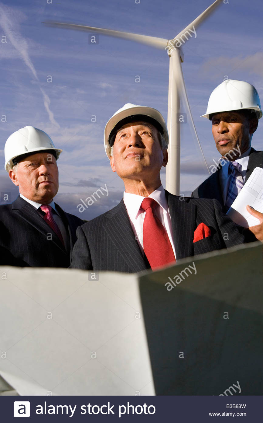 Businessmen inspecting wind power plant - Stock Image