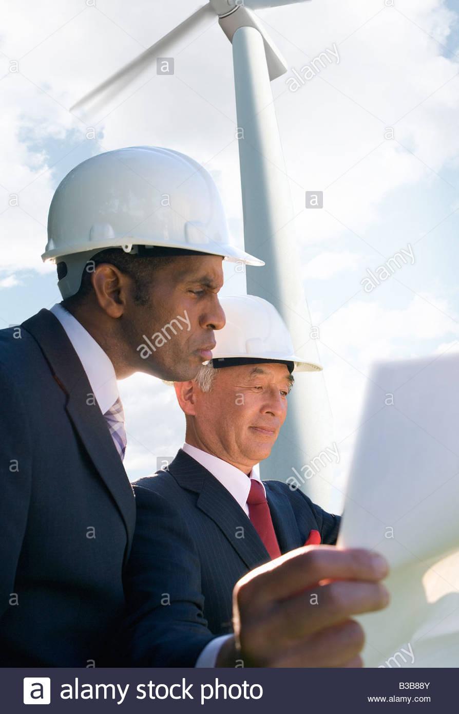 Businessmen inspecting wind power plant - Stock Image