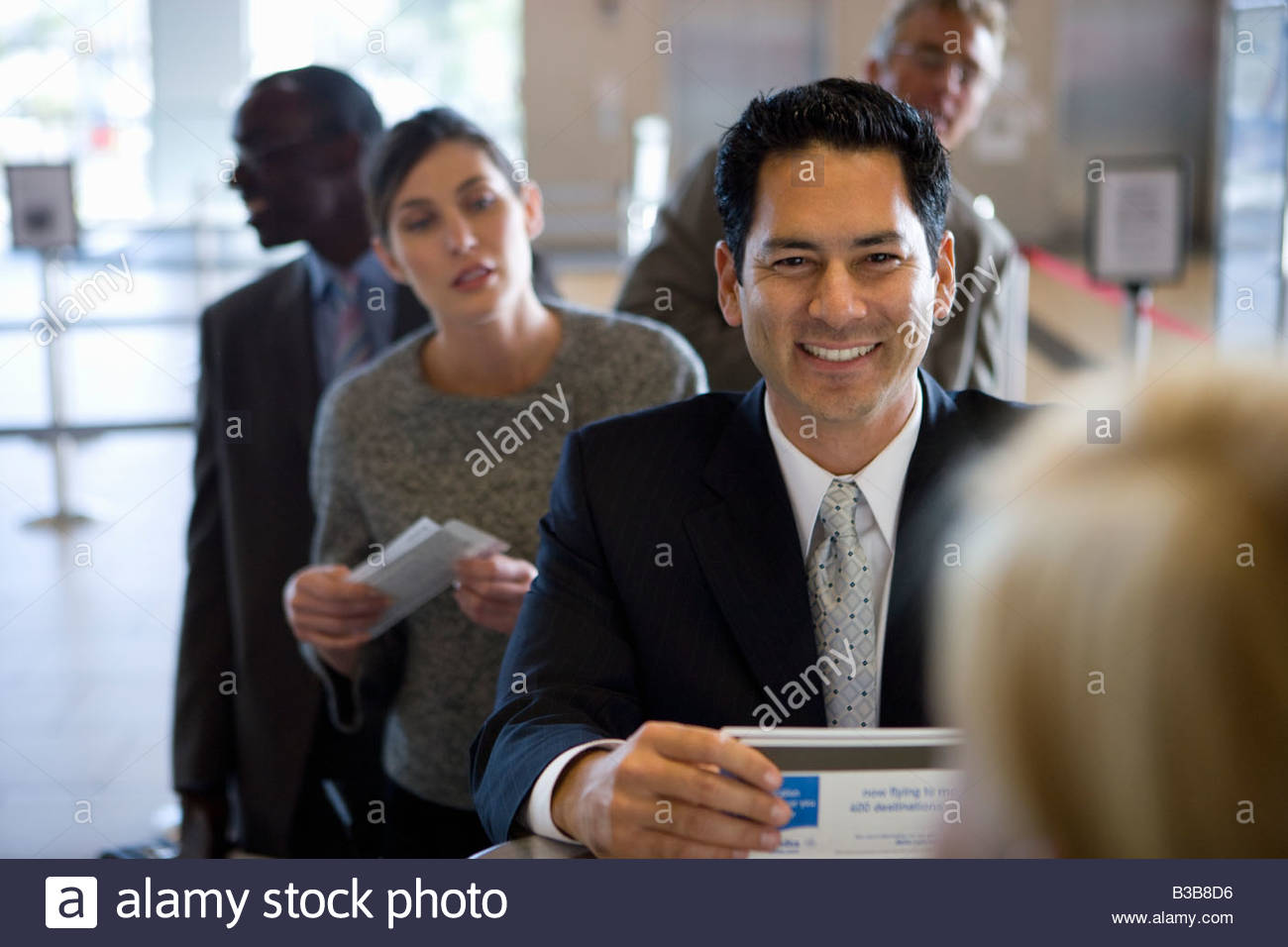 Businesspeople waiting in line in airport - Stock Image