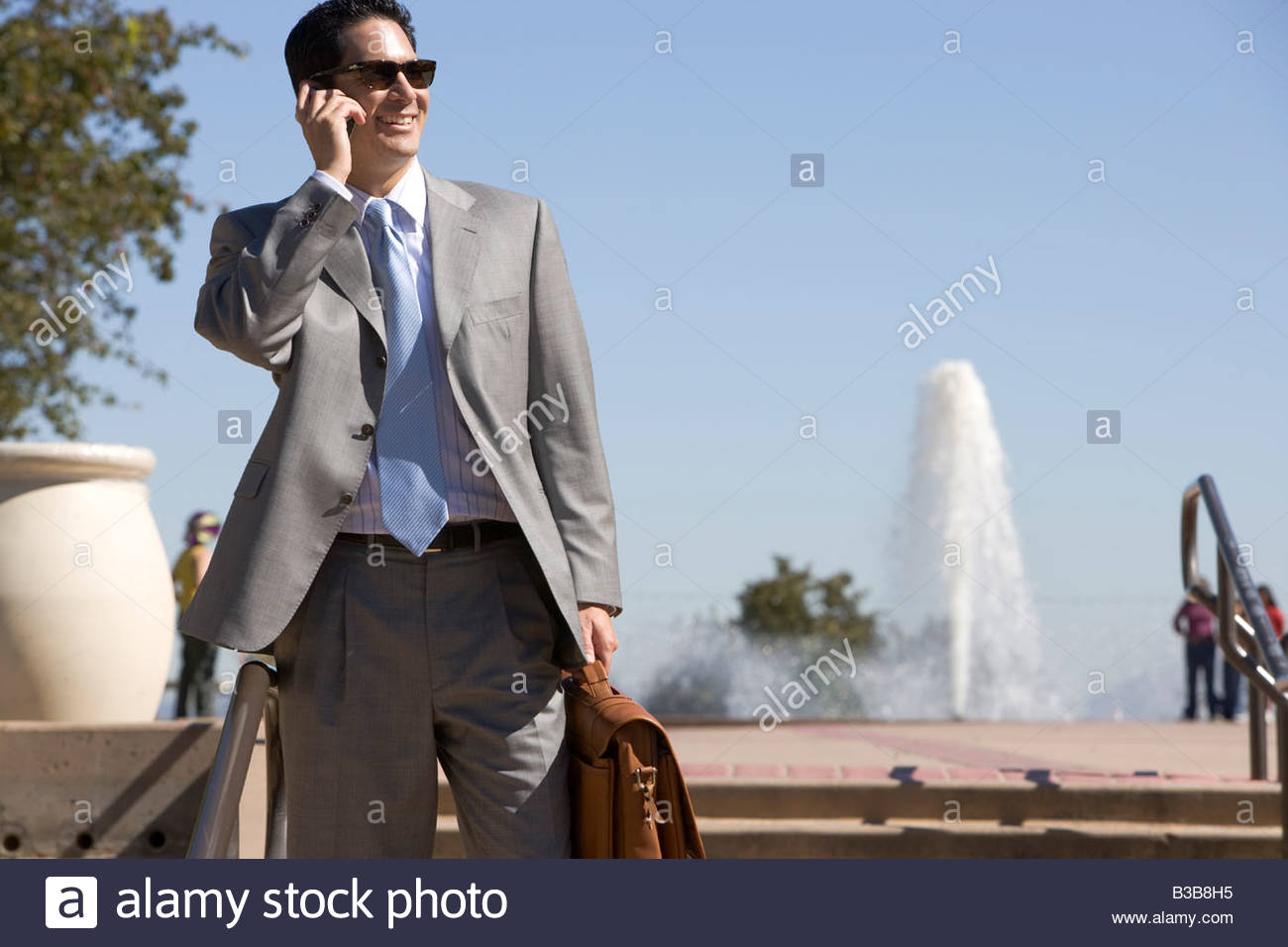 Businessman talking on cell phone outdoors - Stock Image