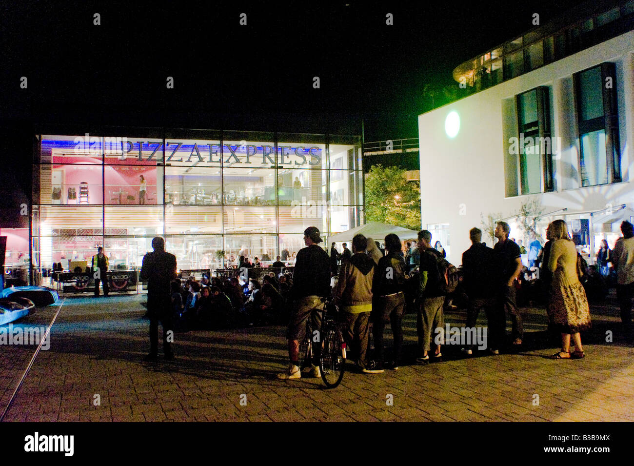 Crowds gather in Brighton Jubilee square for a light show projected on buildings looking towards My hotel and Pizza Stock Photo