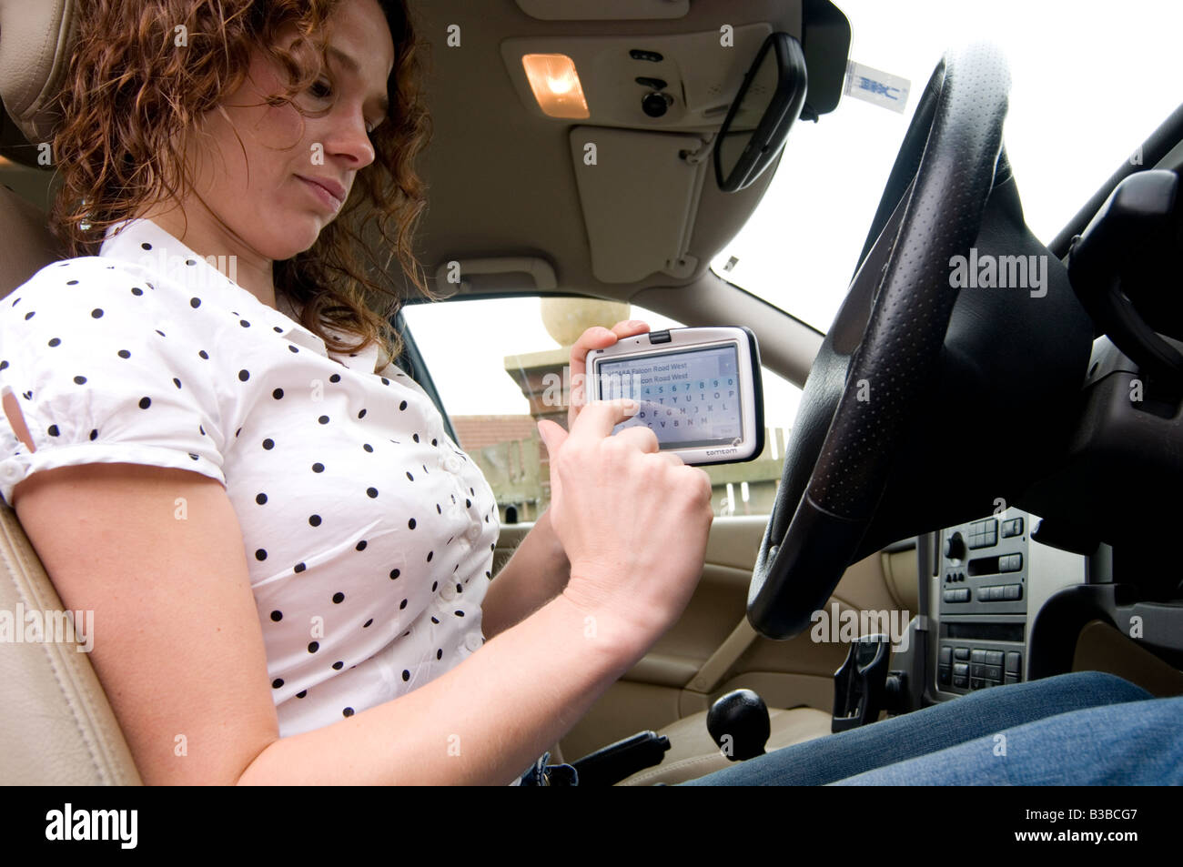 woman using sat nav at wheel of car gps satellite navigation tom tom whilst driving driver cars touch screen directions - Stock Image