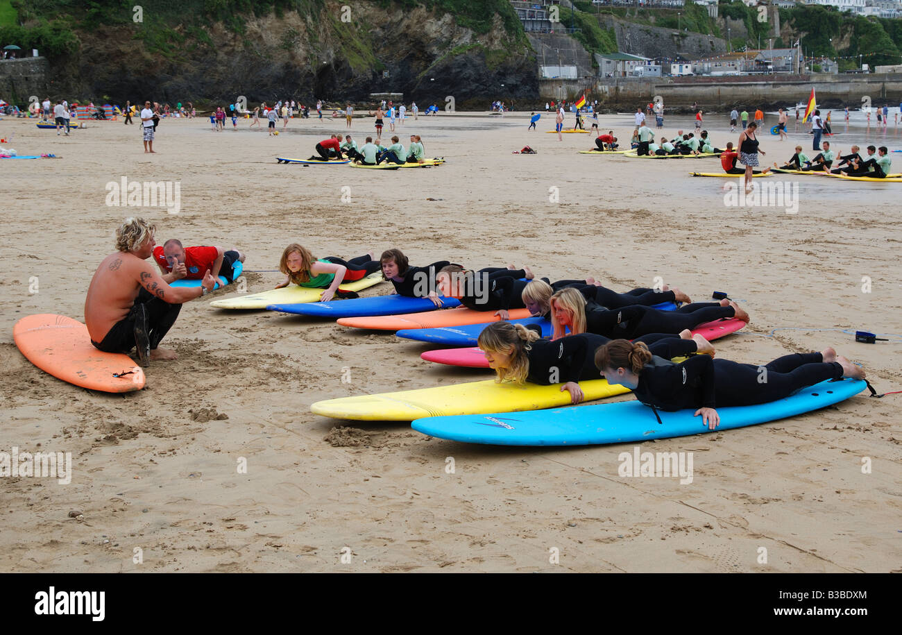 a group of teenage girls having lessons at a surf school on the beach in newquay,cornwall uk - Stock Image
