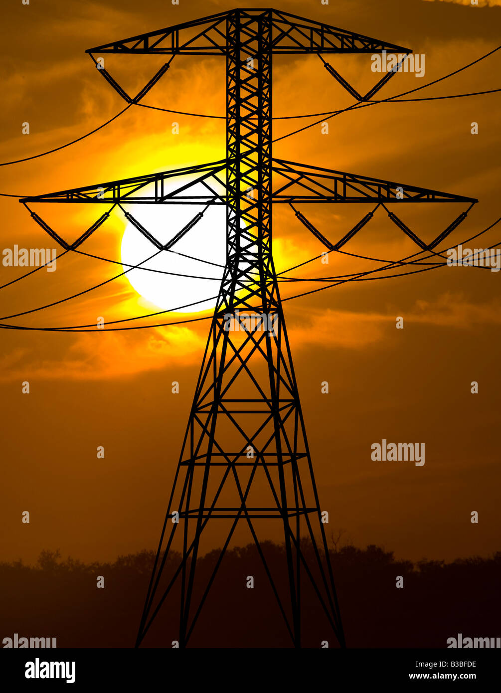 transmission power line tower at sunset - Stock Image