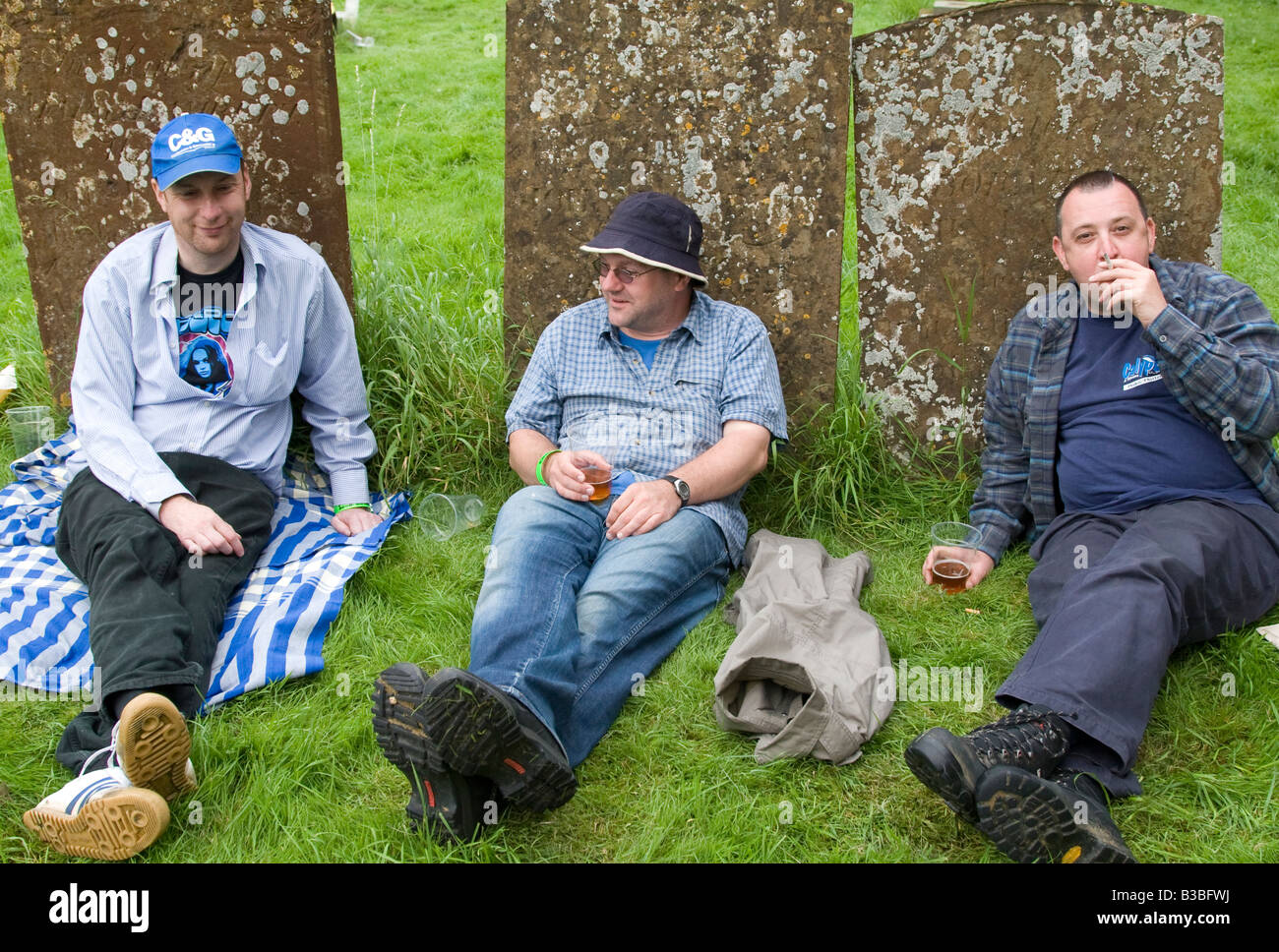 three men drinking in the graveyard in Cropredy village at the time of the 2008 Fairport's Cropredy Convention - Stock Image