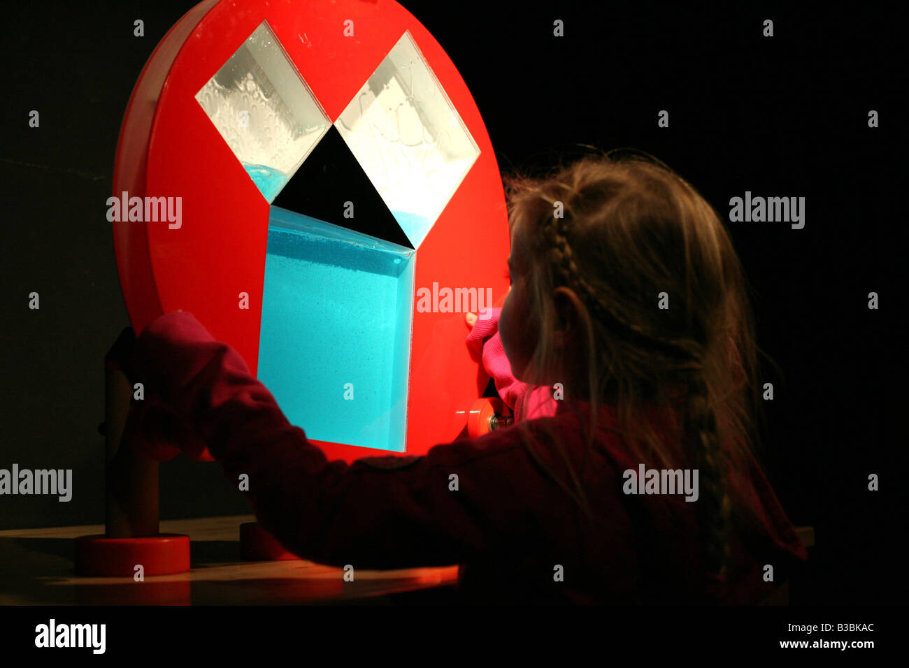 Young visitor studies communicating vessels in Science Centre Spectrum in Deutsches Technikmuseum Berlin, Germany - Stock Image