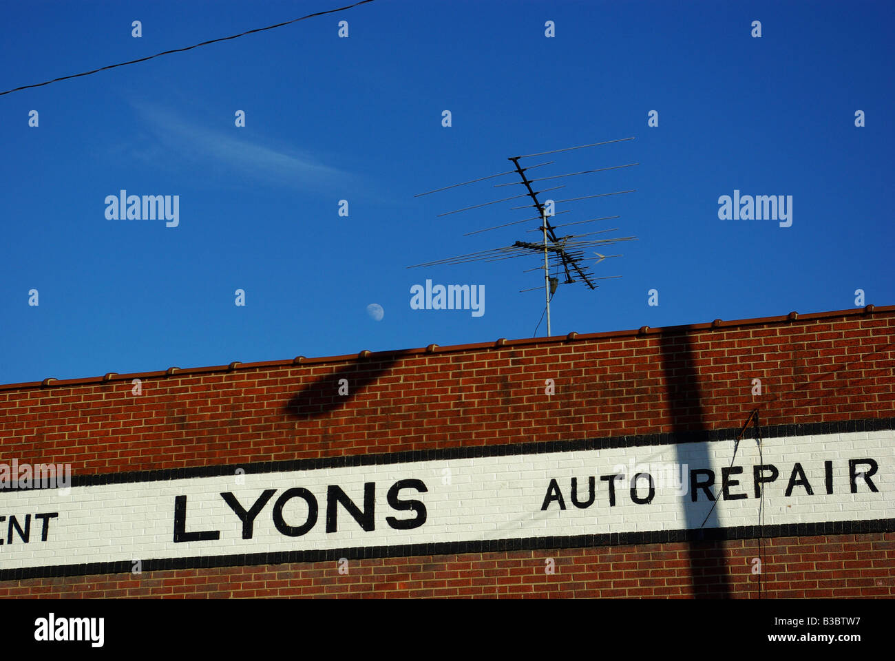 The moon is visible in the sky next to an old style television aerial on an abandoned mid 20th century auto shop. - Stock Image