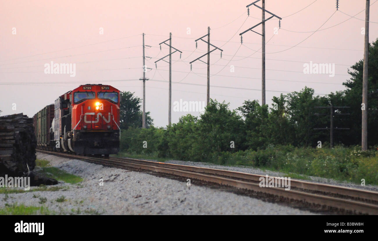 Canadian National CN locomotive and freight train on railroad tracks in a small rural town - Stock Image