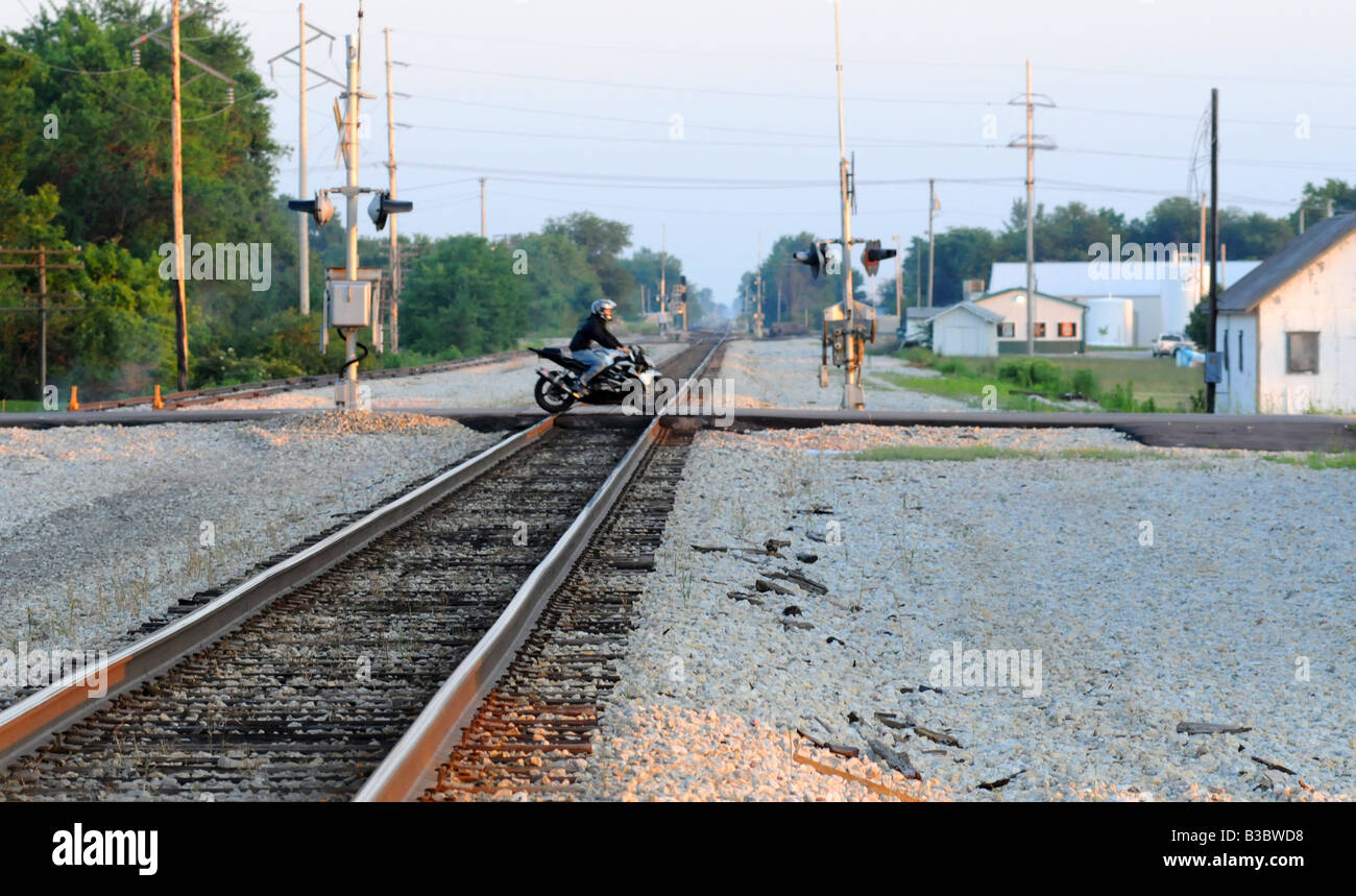A rural railroad crossing of the CN train line being crossed by a motorcycle - Stock Image