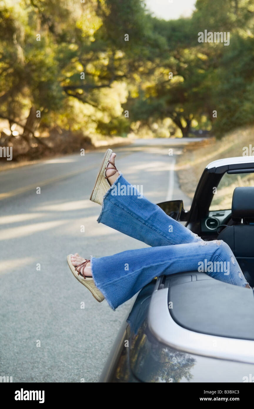 Asian woman's feet hanging out of convertible car Stock Photo