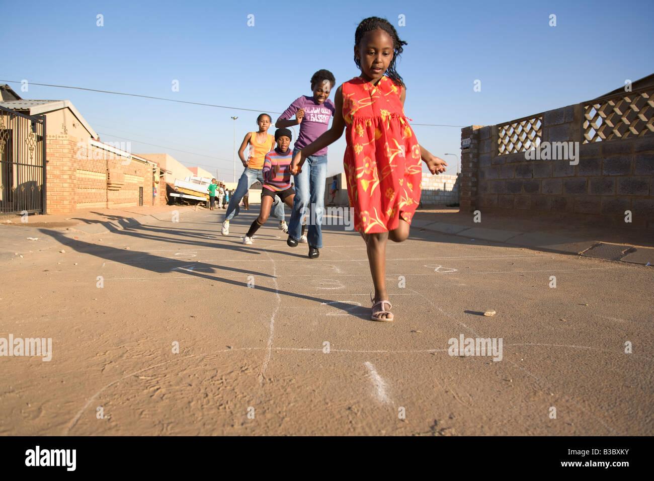 Girls playing hopscotch on street - Stock Image