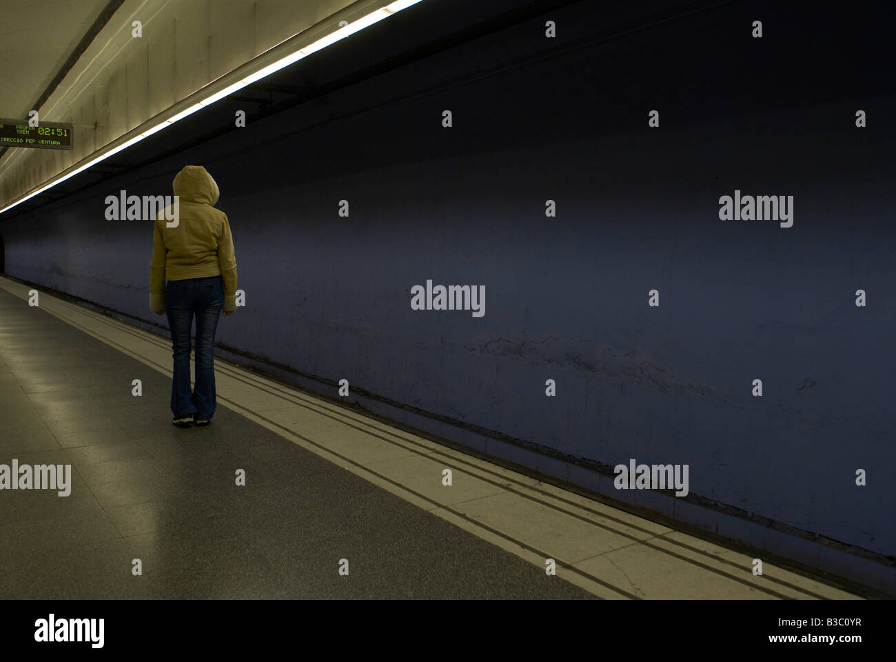 A hooded woman standing on an empty station platform - Stock Image