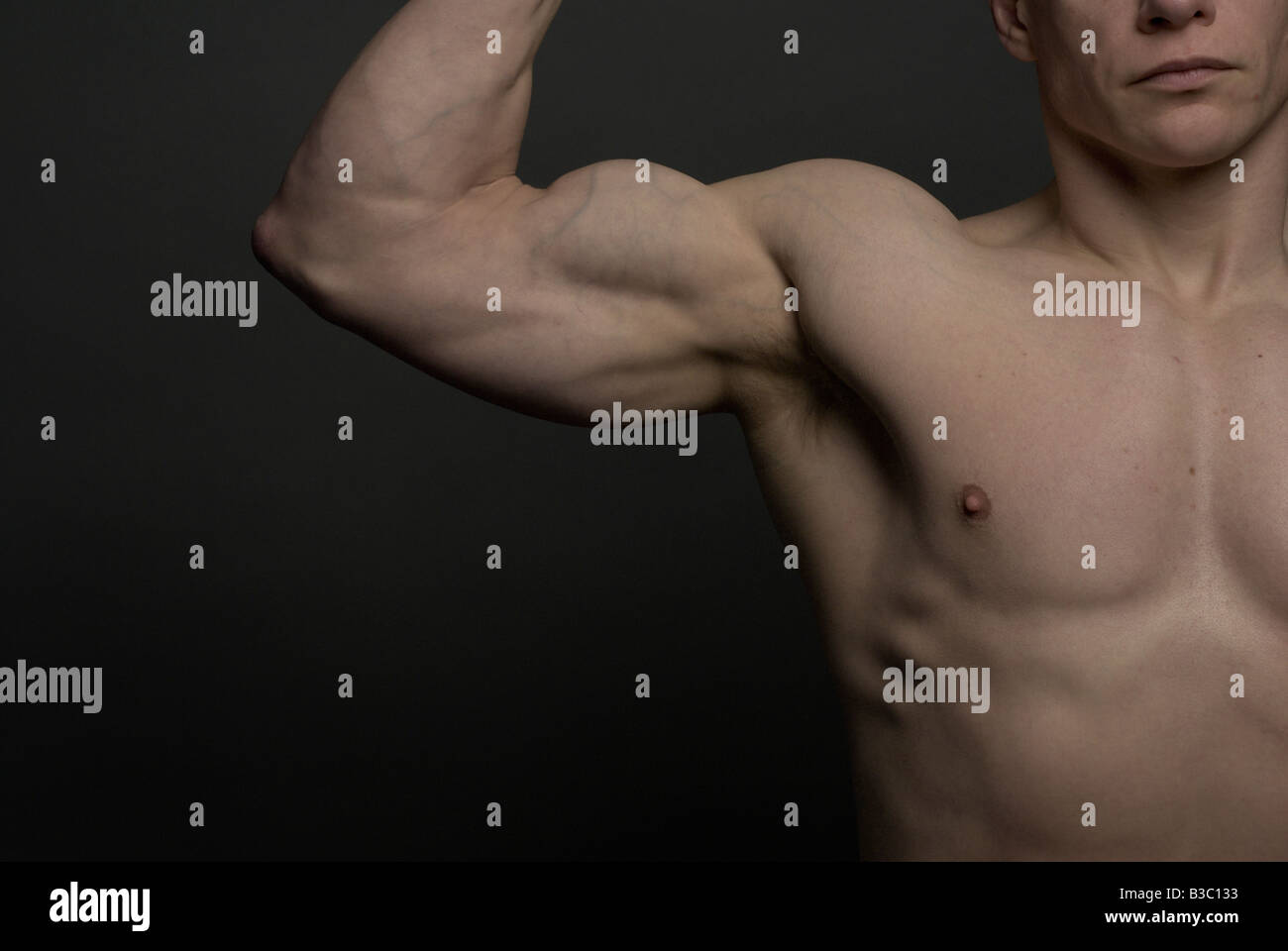 a man tensing his bicep muscle stock photo 19318631 alamy