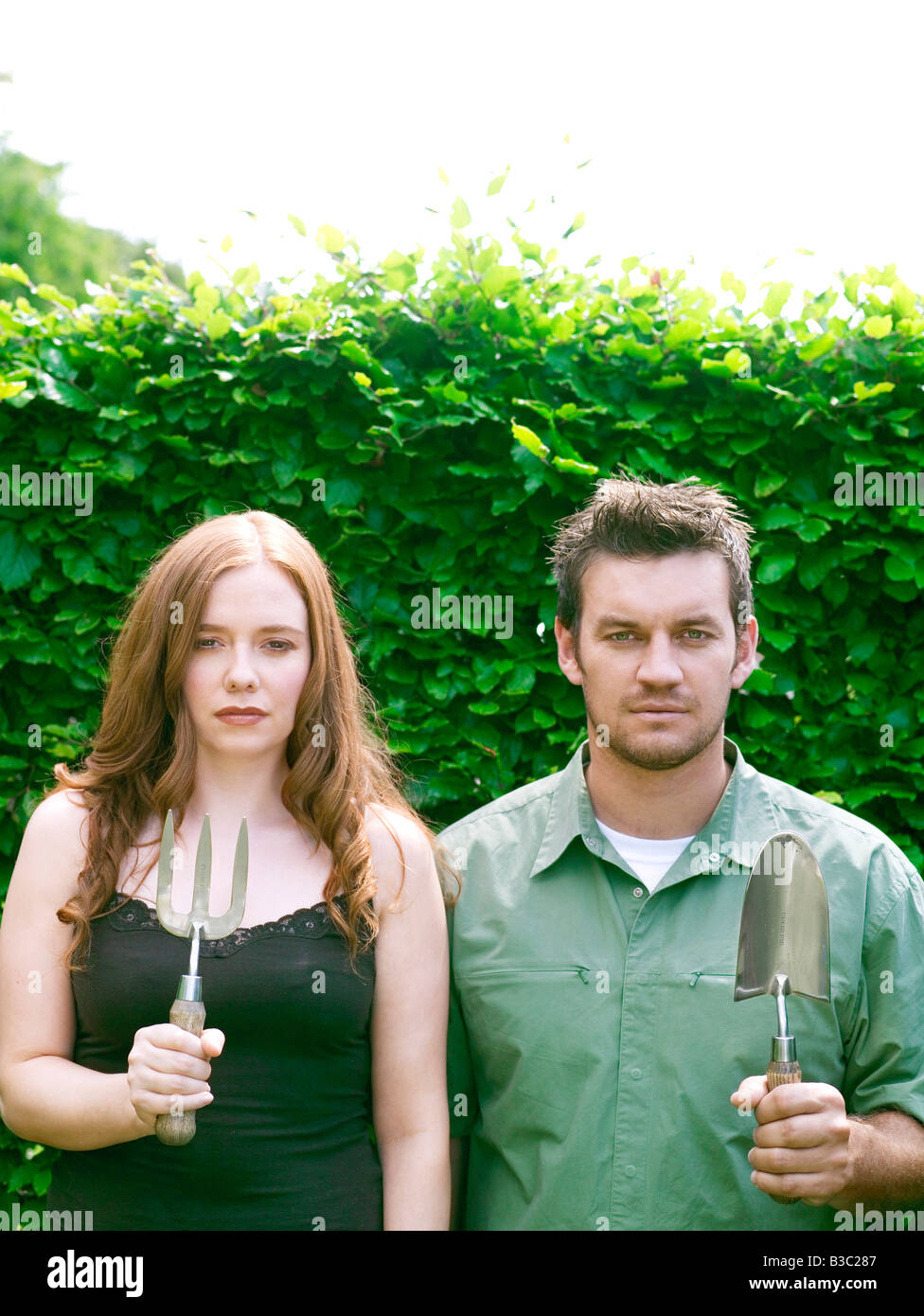 A couple in a garden standing with trowel and fork - Stock Image