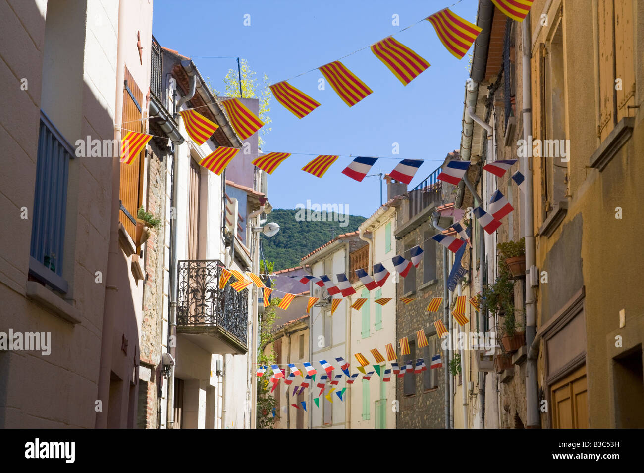 A street is decorated with flags and streamers in both Catalonian and French colours for the French national holiday - Stock Image