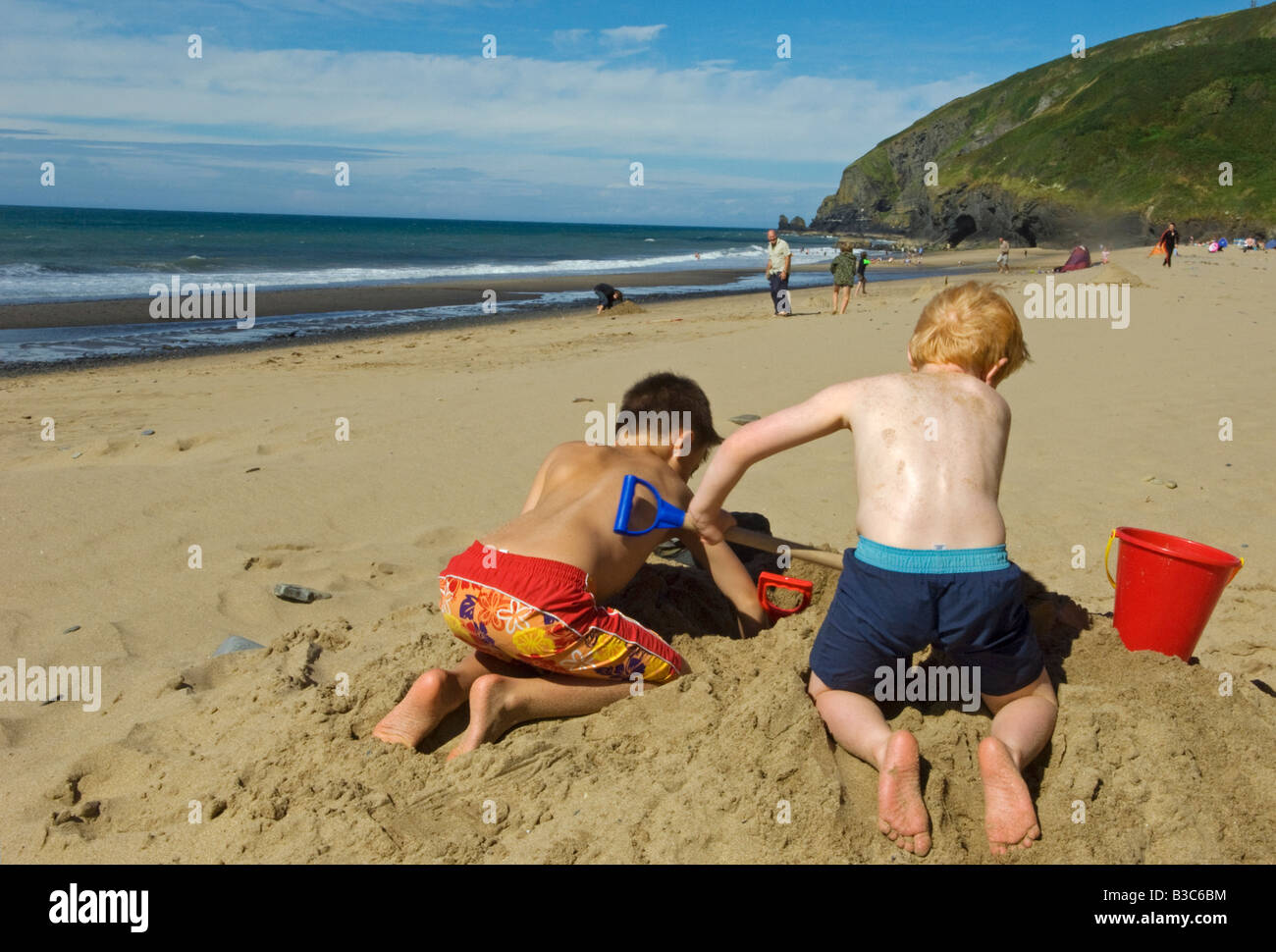UK, Wales, Ceredigion. Two young boys build a sandcastle on Penbryn Beach in Cardiganshire. - Stock Image