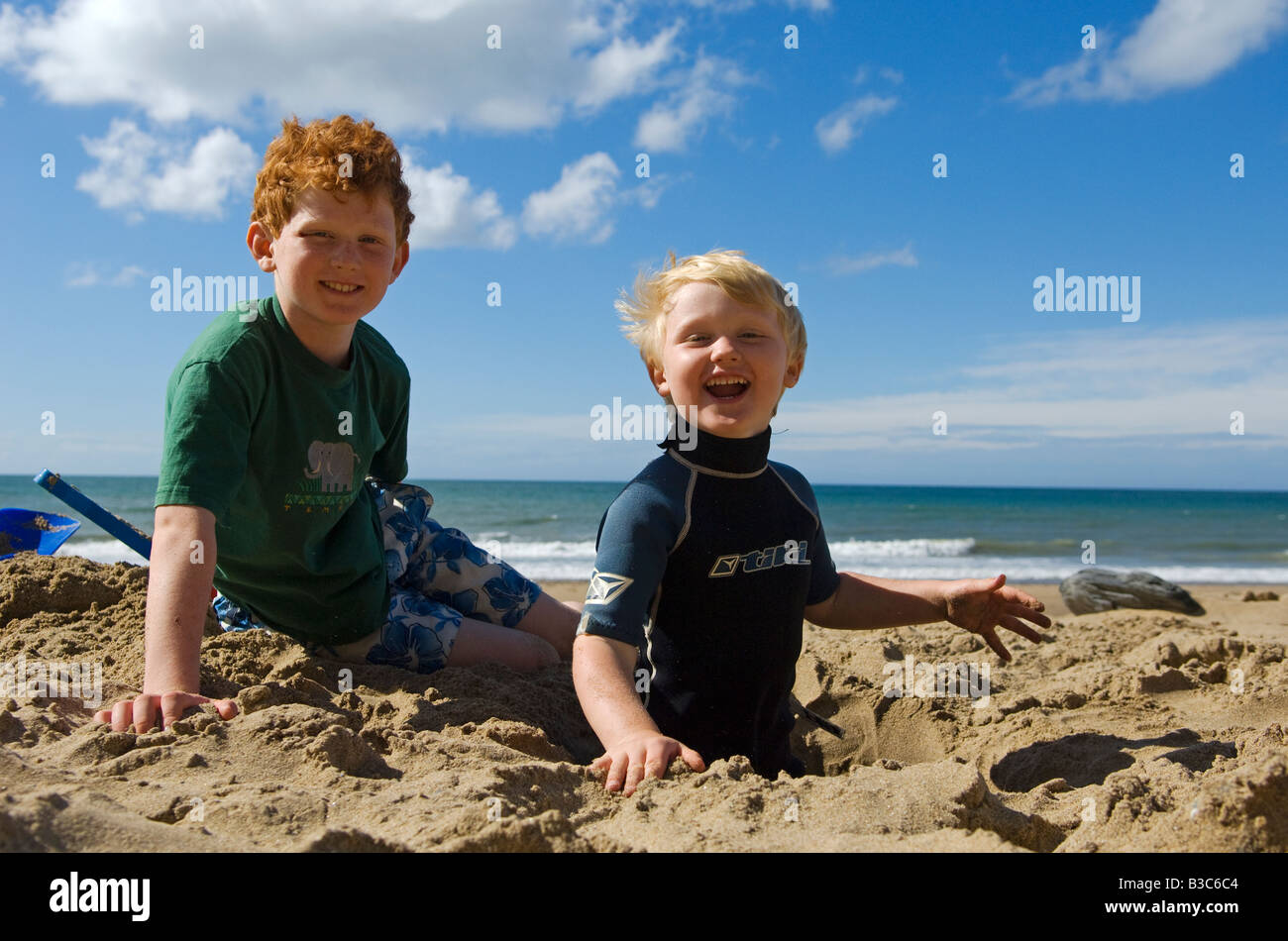 UK, Wales, Ceredigion. Two young boys enjoy playing on Penbryn Beach in Cardiganshire (MR). - Stock Image