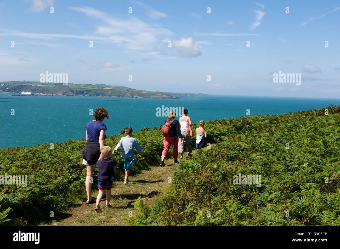 UK, Wales, Pembrokeshire. A family walks along the Pembrokeshire Coastal Path around Dinas Head with views of Fishguard - Stock Image