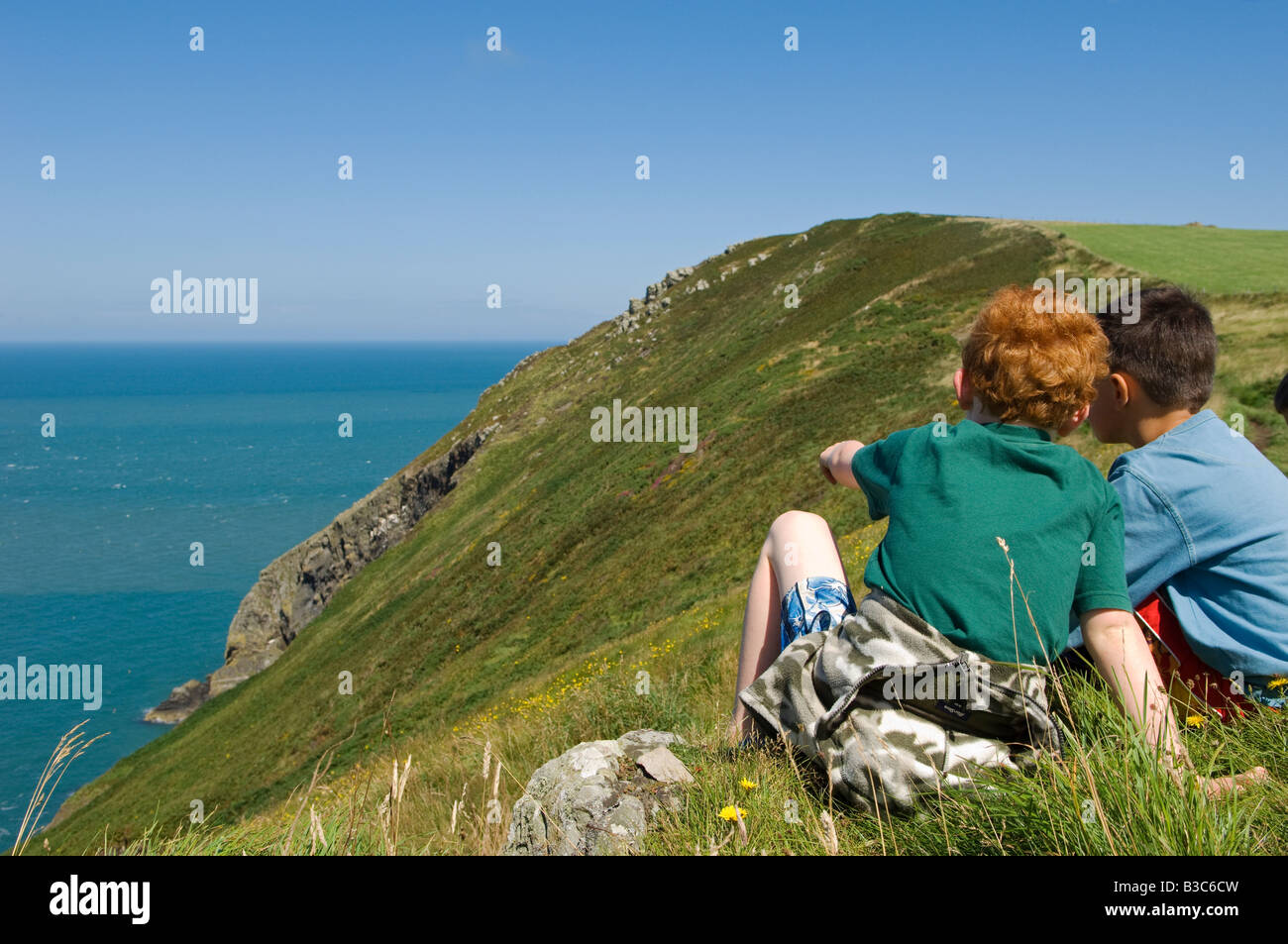 UK, Wales, Pembrokeshire. Two boys sit looking out over Fishguard Bay and the Irish Sea from the Pembrokeshire Coastal - Stock Image