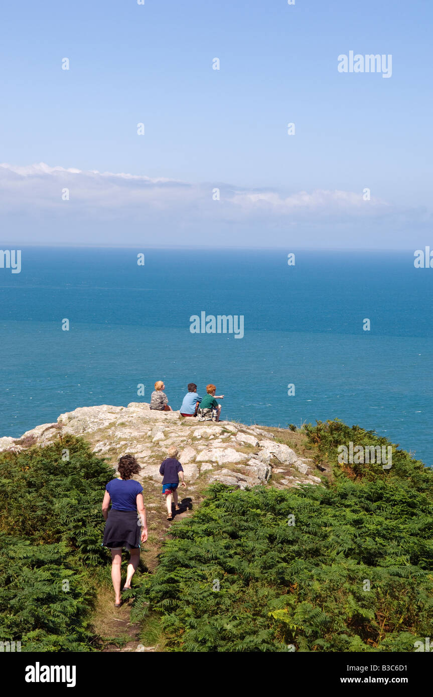 UK, Wales, Pembrokeshire. Three boys sit looking out over Fishguard Bay and the Irish Sea from the Pembrokeshire - Stock Image