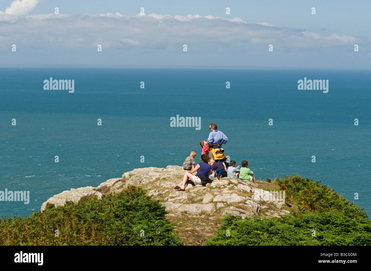 UK, Wales, Pembrokeshire. A family look out over Fishguard Bay and the Irish Sea from the Pembrokeshire Coastal - Stock Image