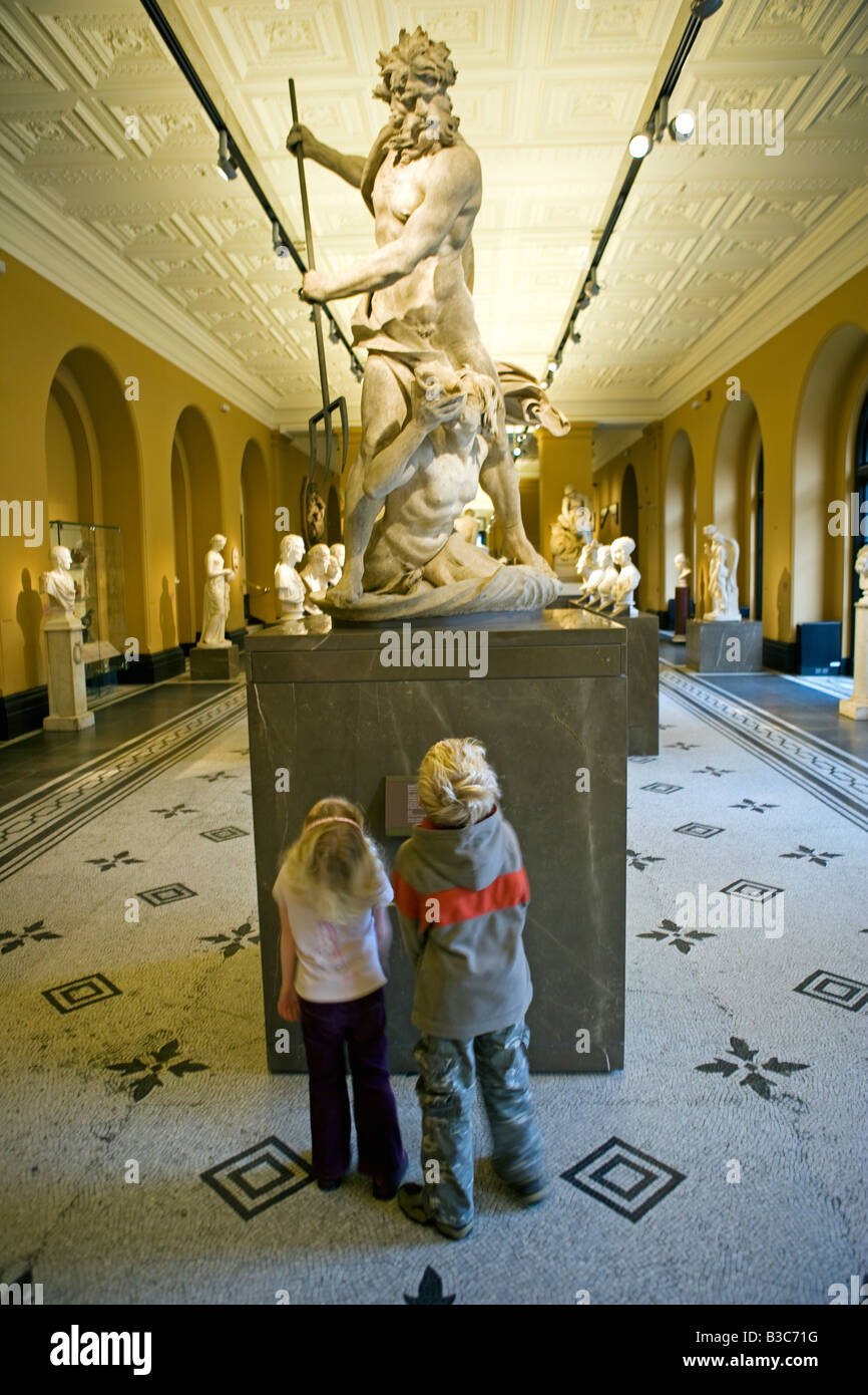 England, London, Victoria and Albert Museum. A brother and sister look up at a classically carved statue in the - Stock Image