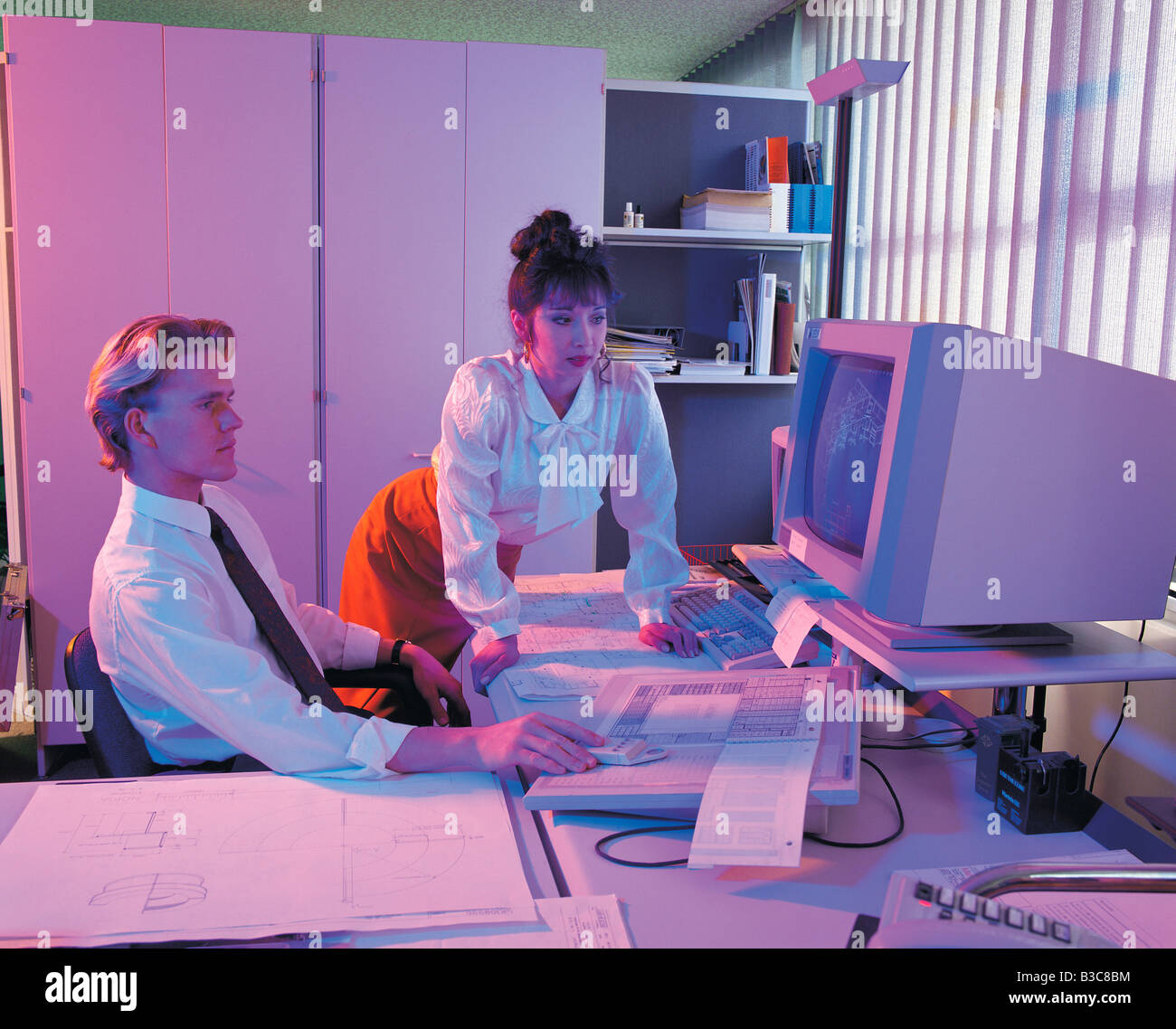 Businesspeople watching blueprints in computer - Stock Image