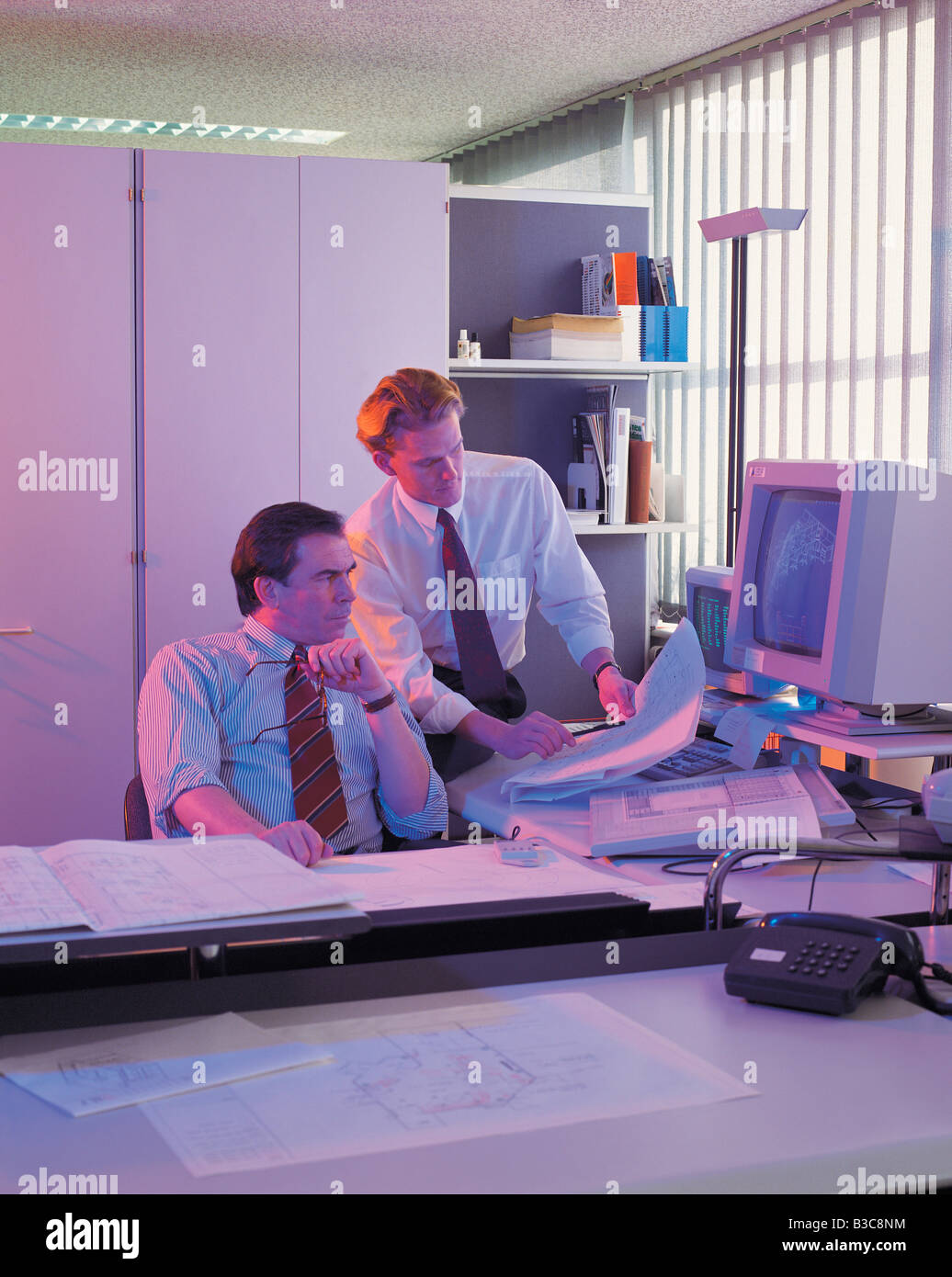 Businesspeople watching blueprints in office - Stock Image