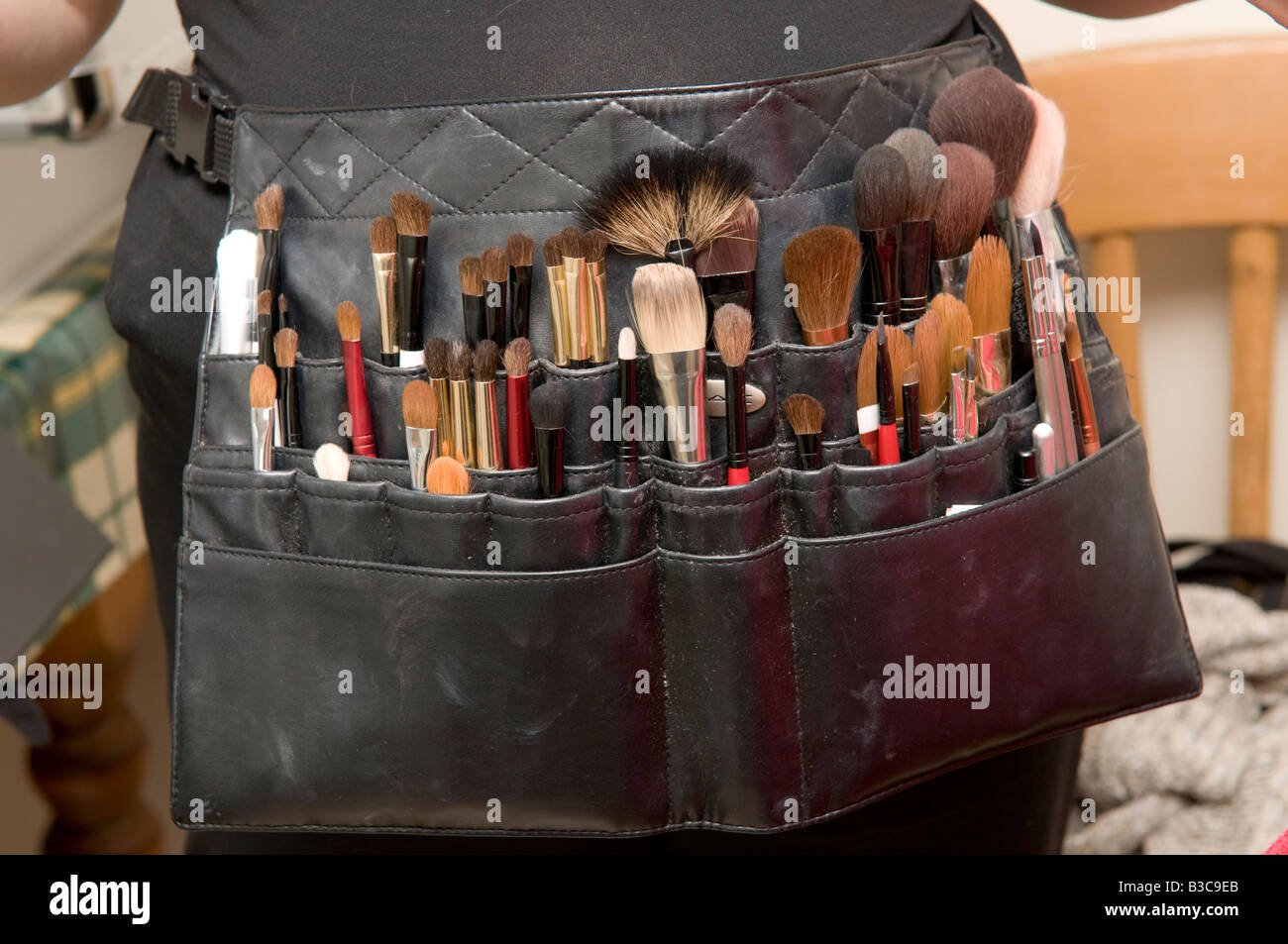 Make up woman's persons beautician pouch bag with her array of brushes used for applying makeup to a woman's - Stock Image