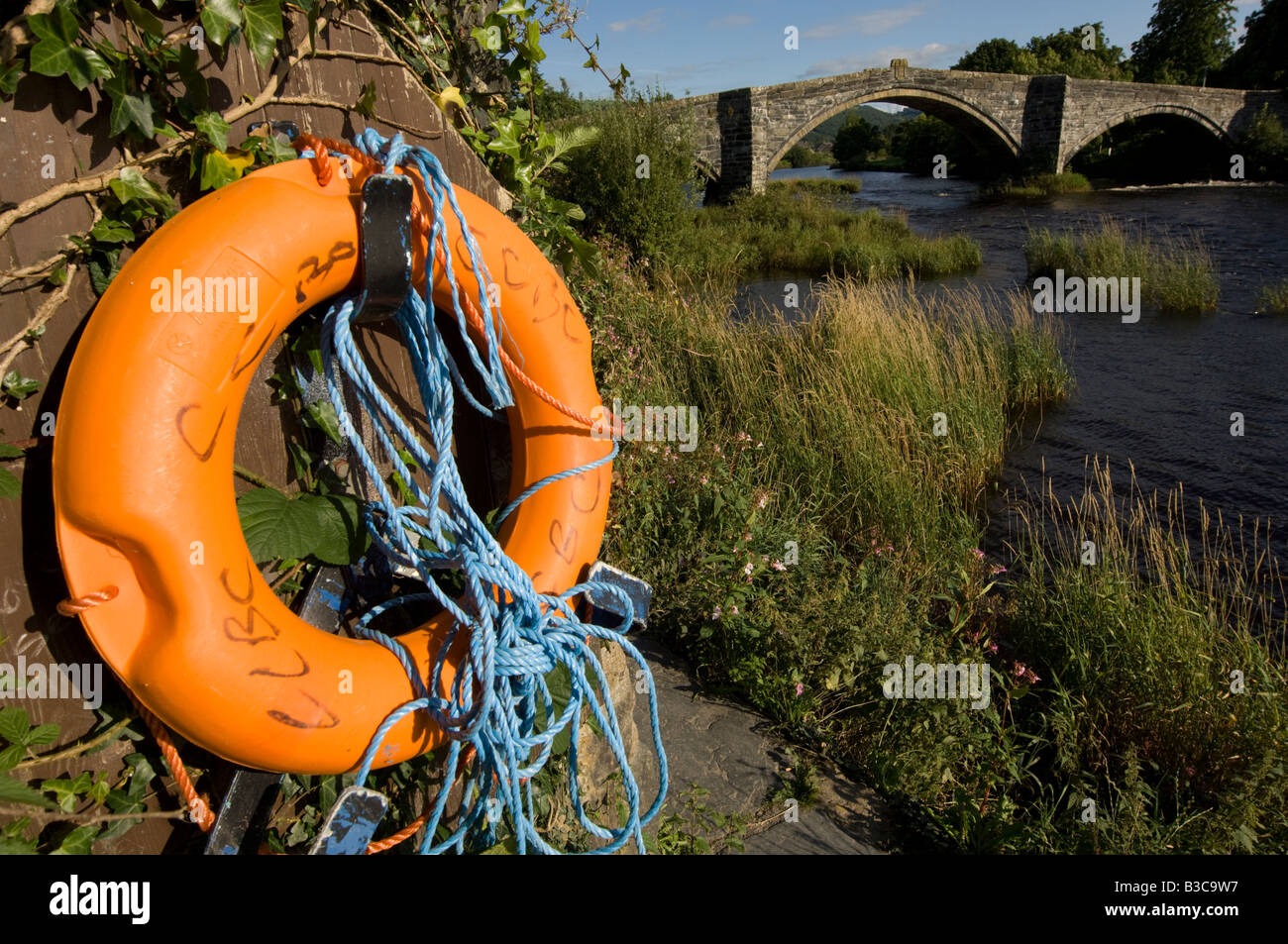 Orange lifebelt life saving equipment by the River Conwy at Llanrwst  north Wales with the old bridge in the background - Stock Image