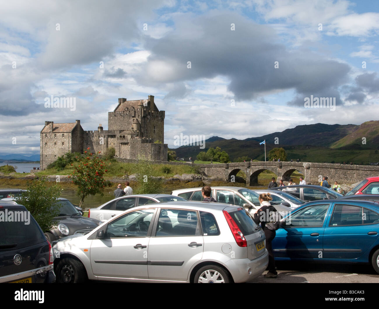 The tourist cars in the car park of Eilean Donan Castle. - Stock Image