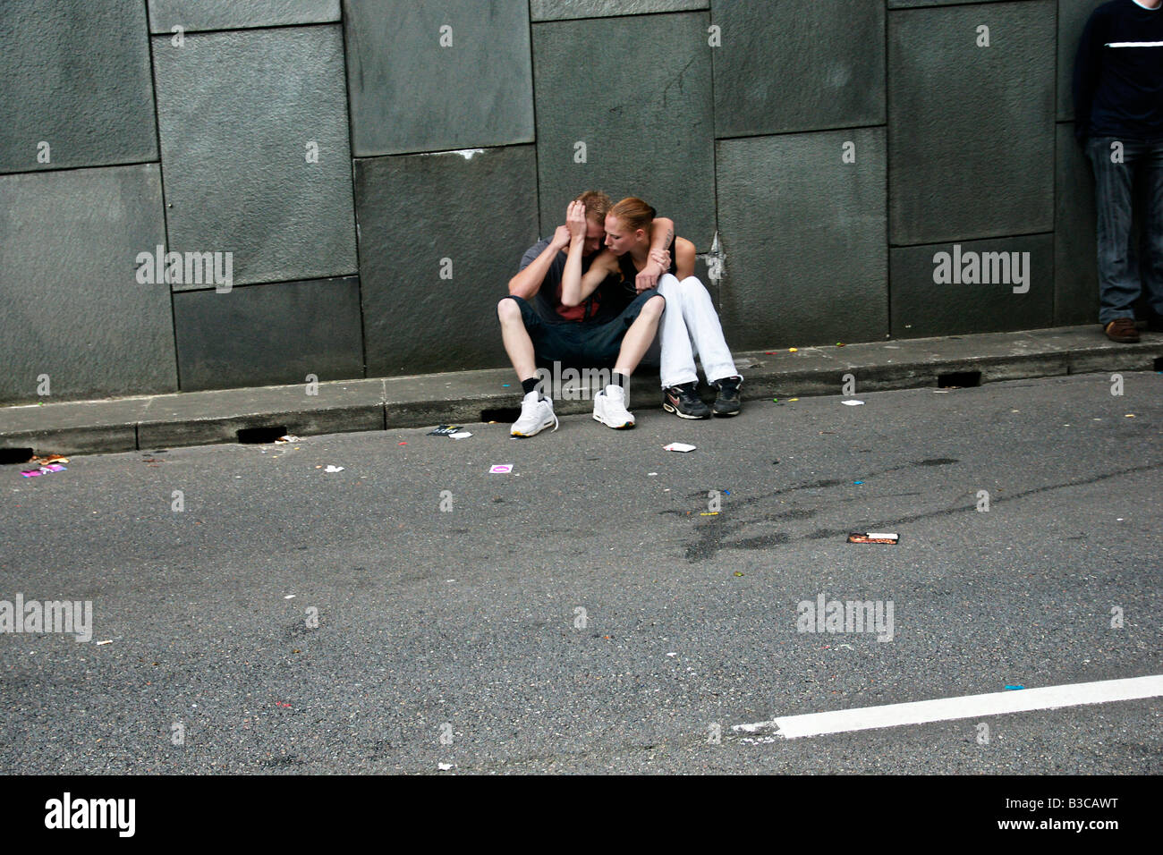 Desperate couple sitting in front of depressive grey concrete wall while paritally obscured man standing nearby. - Stock Image