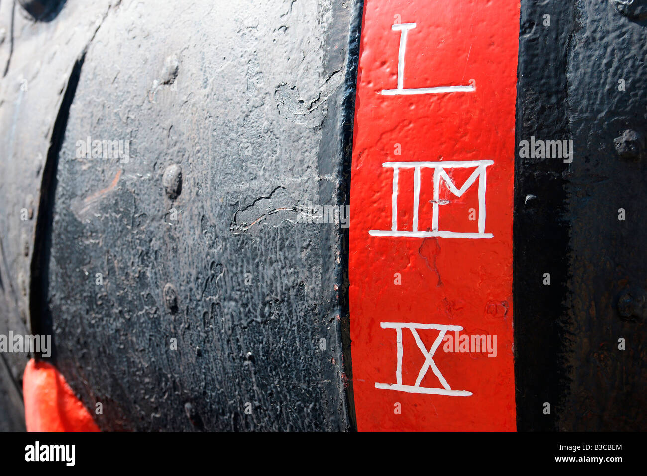 Red stripe with white digits on black metal of a ship hull - one of machines on display at Maritiem Museum of shipping - Stock Image