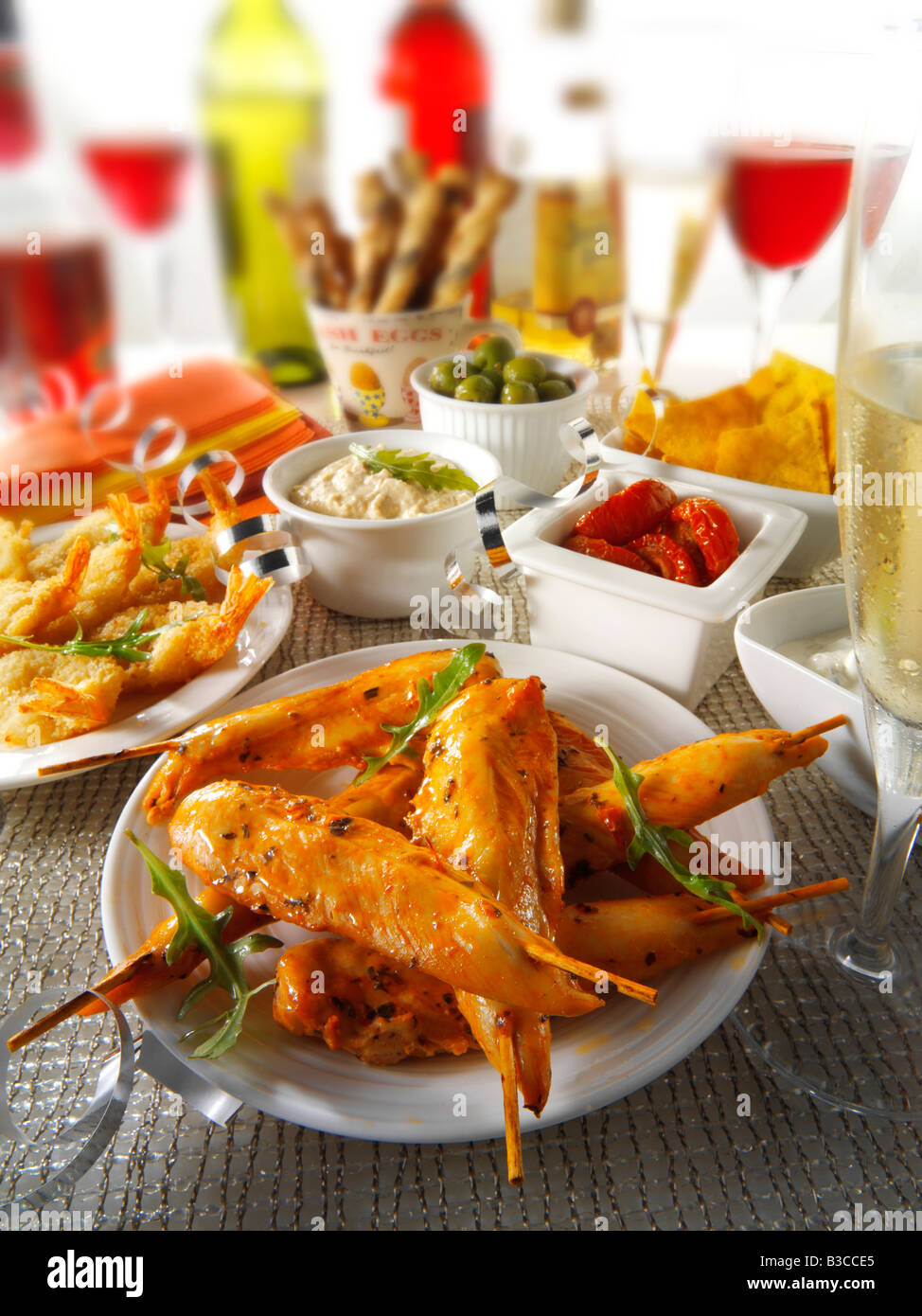party food setting with marinated chicken skewers, sun dried tomatoes dip - Stock Image