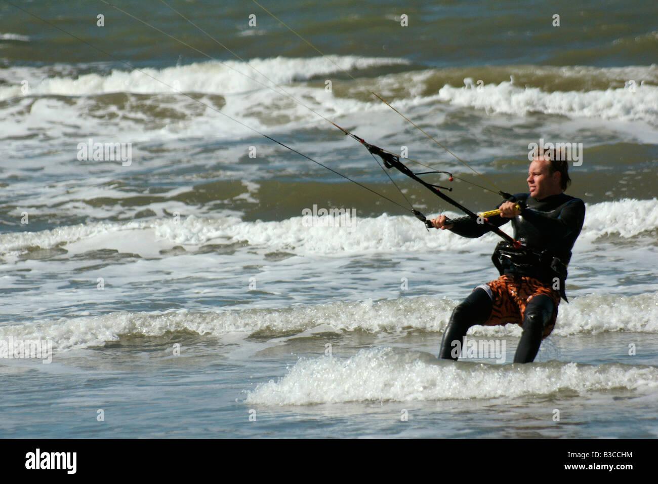 Man in neophrene suit surfing powerkite parafoil in sea high speed at Hoek van Holland, Netherlands - Stock Image