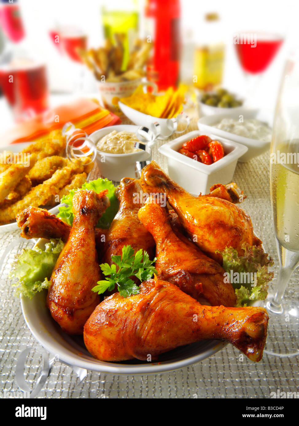 party food setting with chicken drumsticks, goujons  and sun dried tomatoes dip - Stock Image