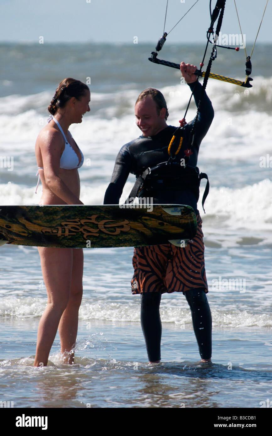 Man in neophrene suit surfing powerkite parafoil in sea talking to woman in swimmingsuit at Hoek van Holland beach, - Stock Image