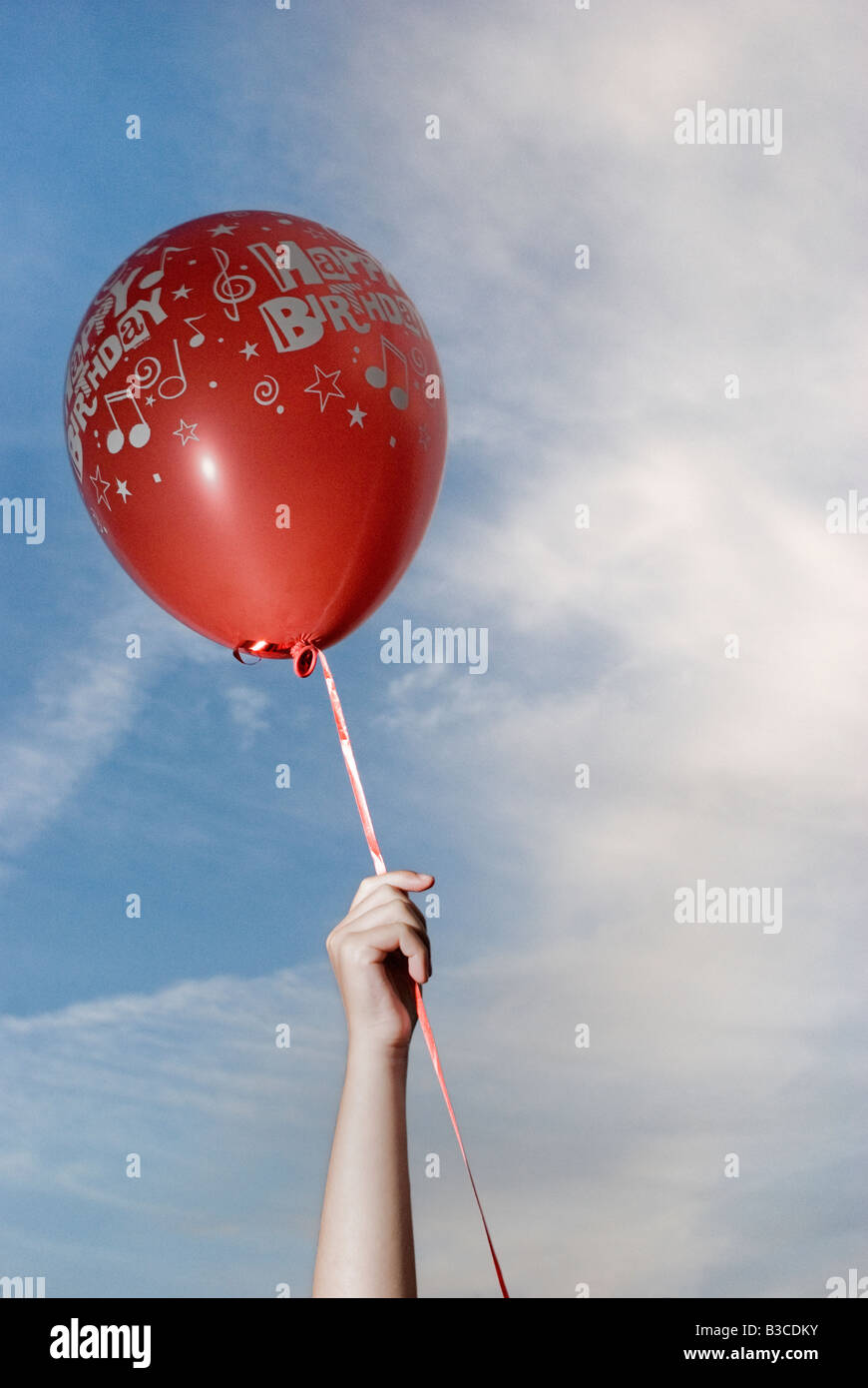 child holds red balloon - Stock Image