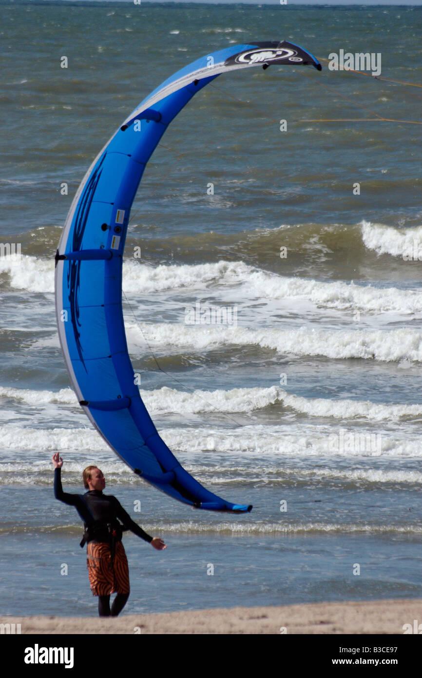 Man alone flying blue parafoil powerkite kite on beach sea shore sand water in wind at Hoek van Holland, Netherlands - Stock Image