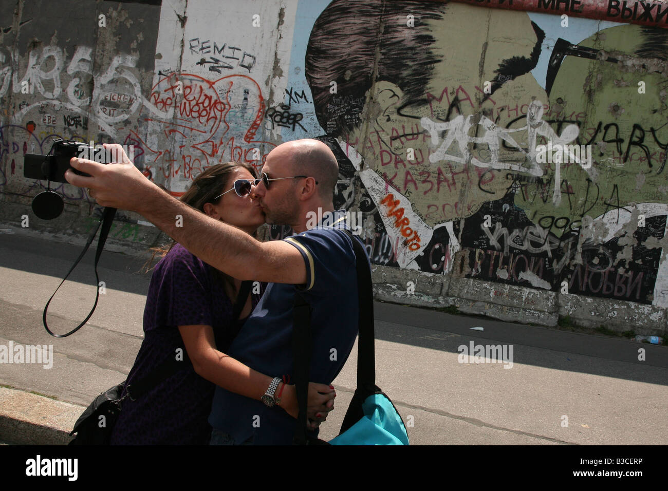 Couple kissing in front of Brezhnev and Honecker's kiss pictured on the Berlin Wall in East Side Gallery in - Stock Image