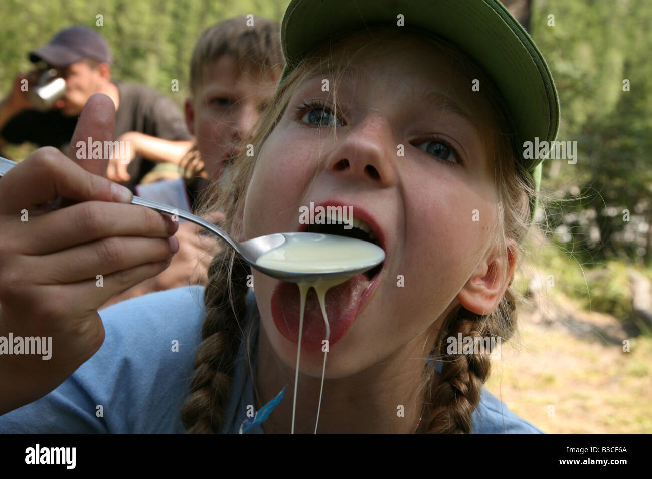 Young girl eating the spoon of condensed milk during a trekking in the Altai Mountains, Russia Stock Photo
