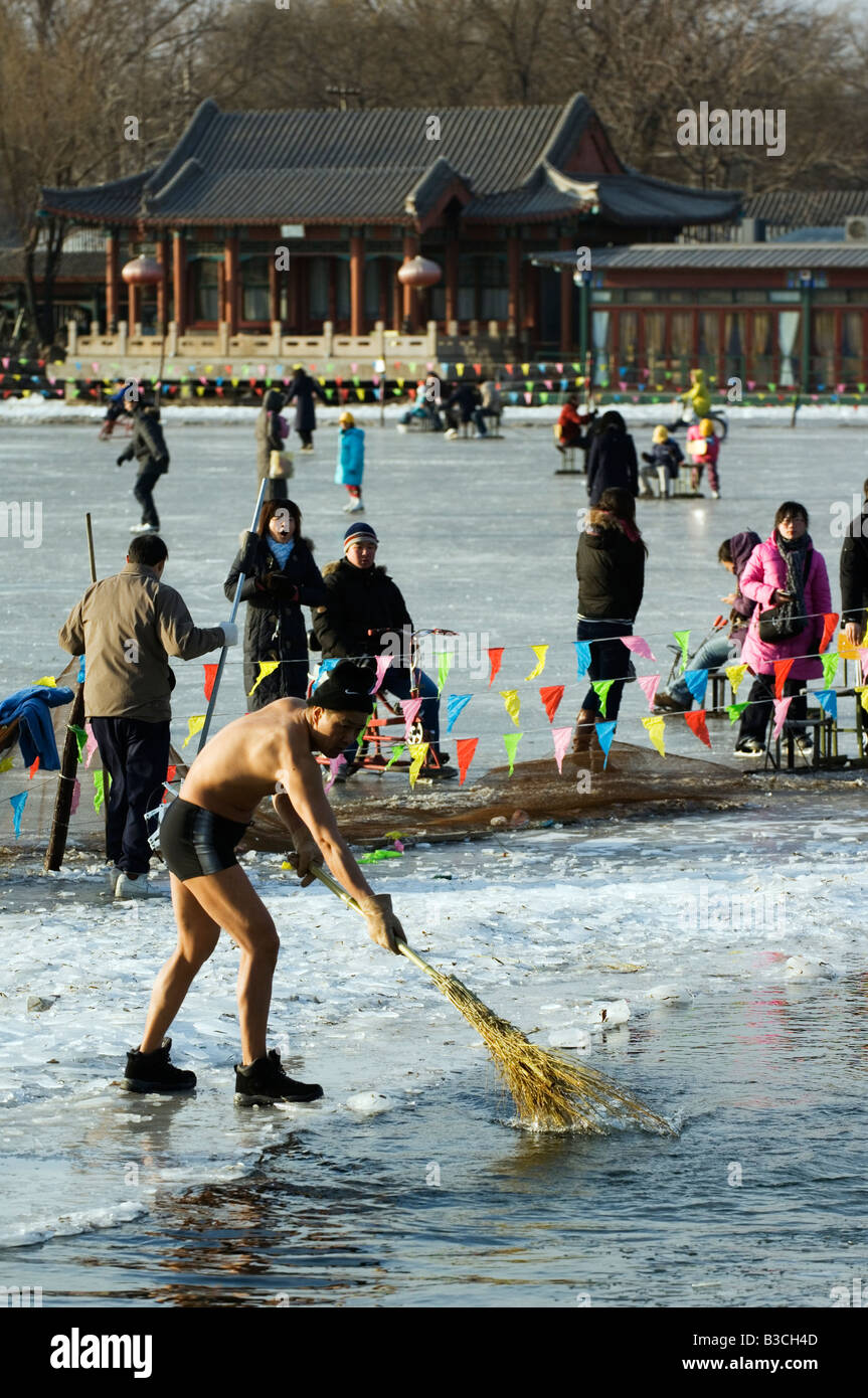 China, Beijing, Houhai area. A man in shorts sweeping ice from the lake in preparation for winter swimming. - Stock Image