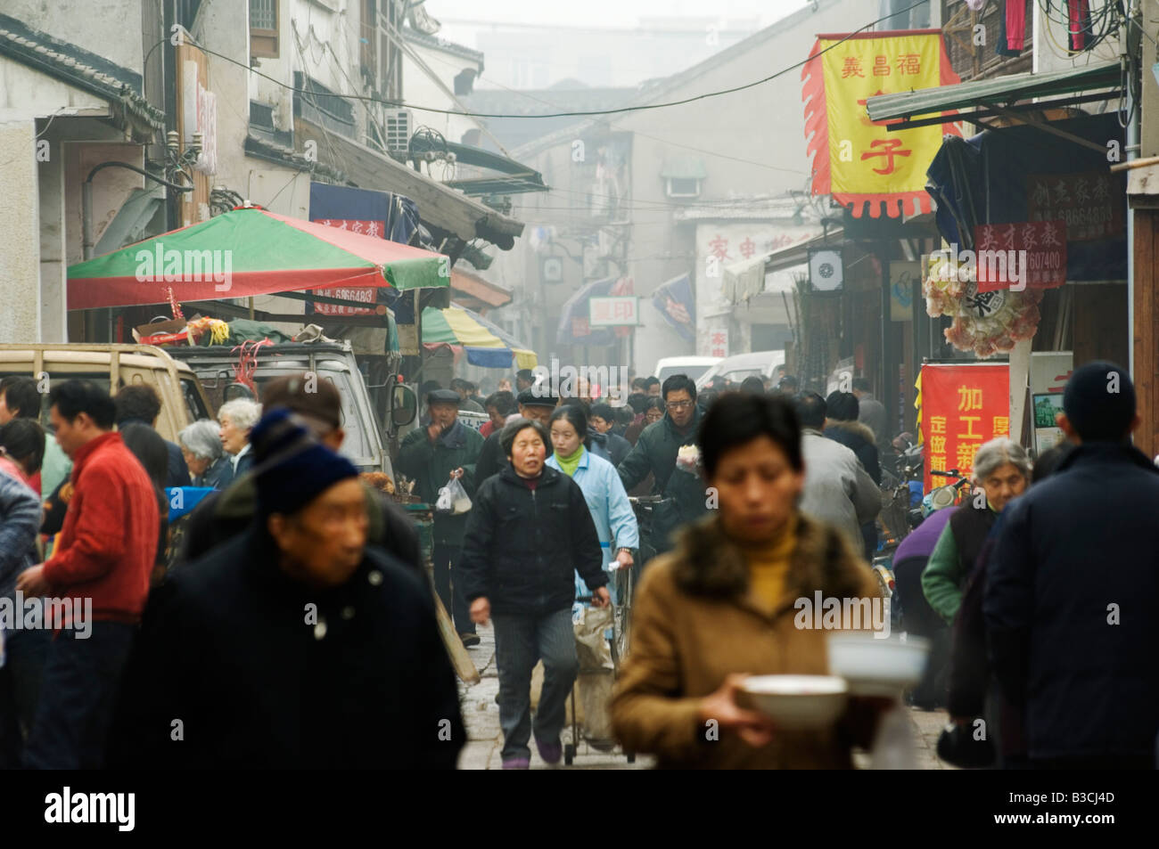 China, Jiangsu Province, Suzhou City. A woman carrying bowls of noodles down a busy street - Stock Image