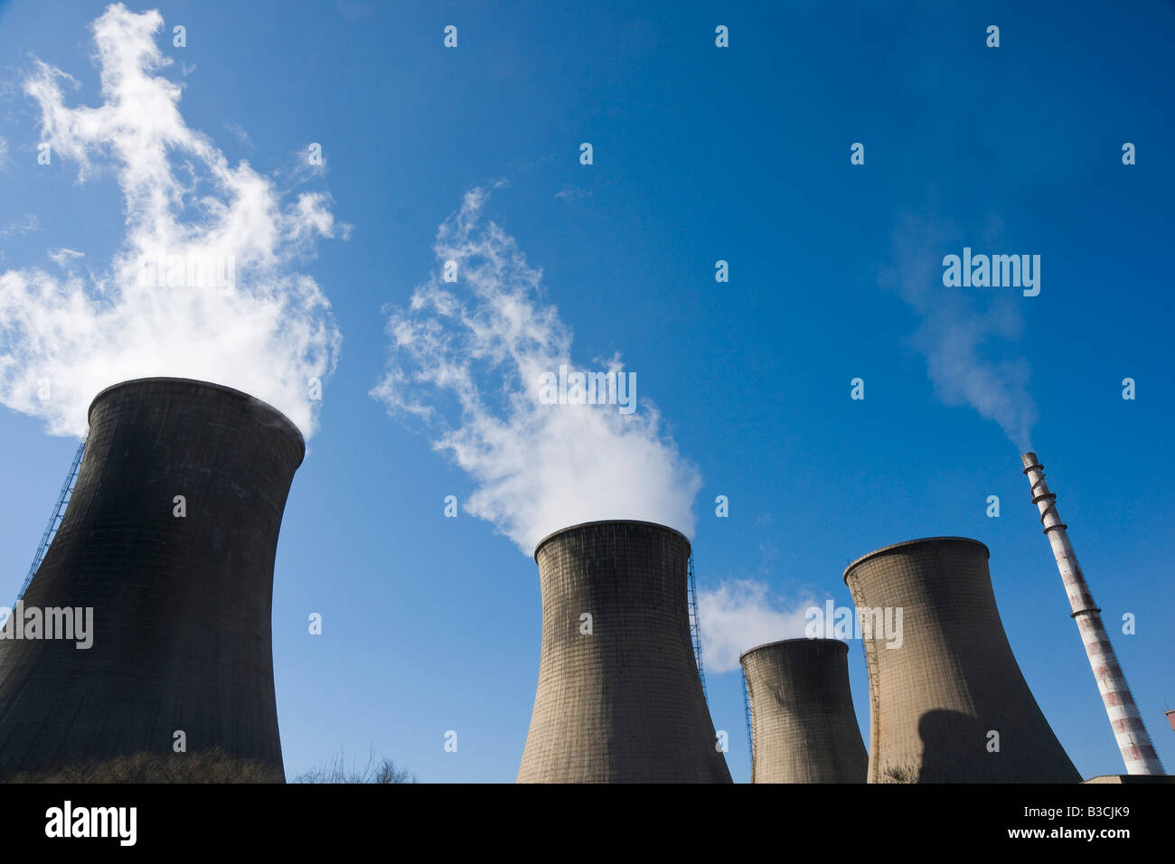 coal fired power station with cooling towers releasing steam into atmosphere - Stock Image