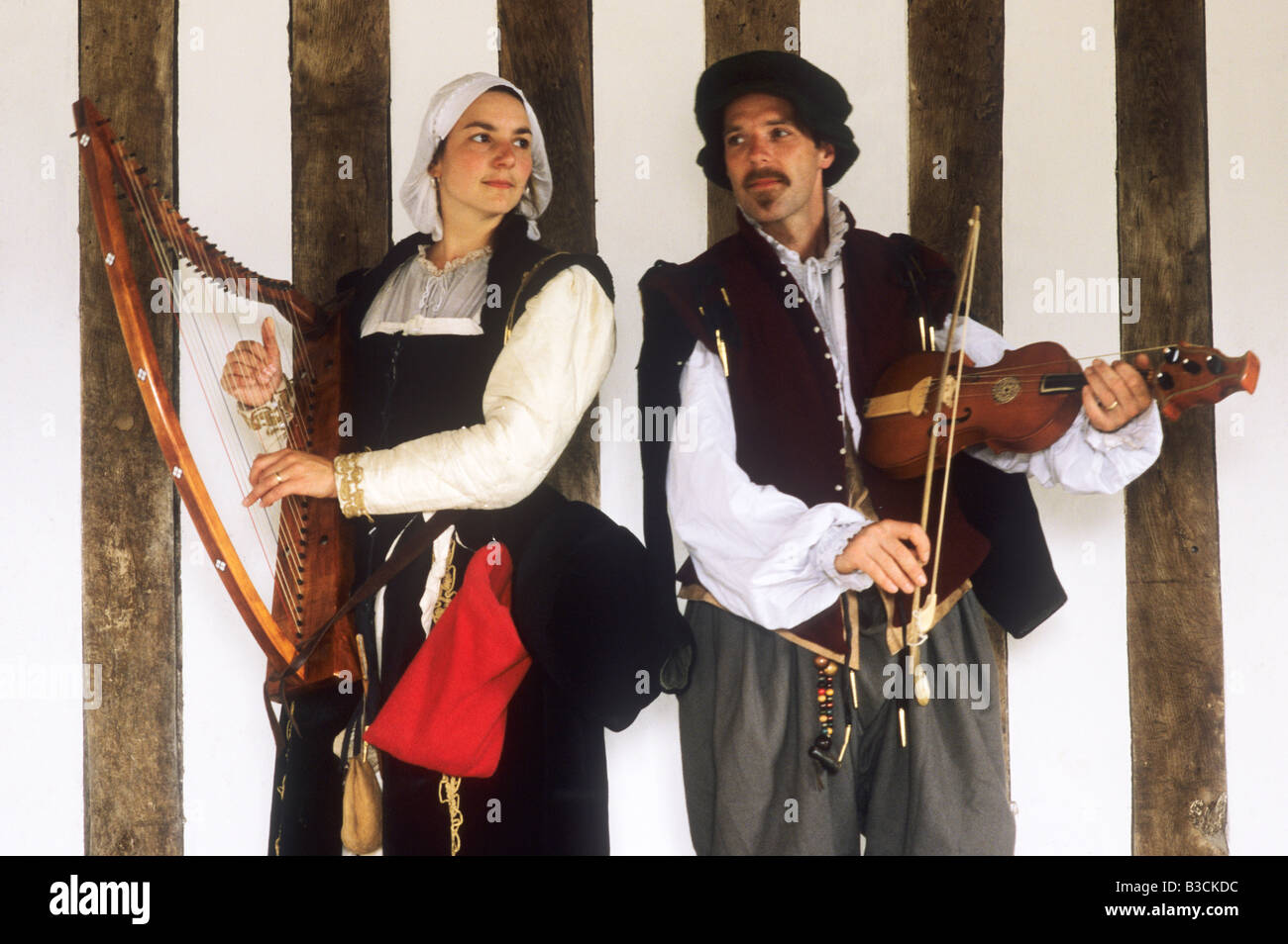 Historical re-enactment Elizabethan musicians musician music musical instrument instruments man woman playing harp - Stock Image