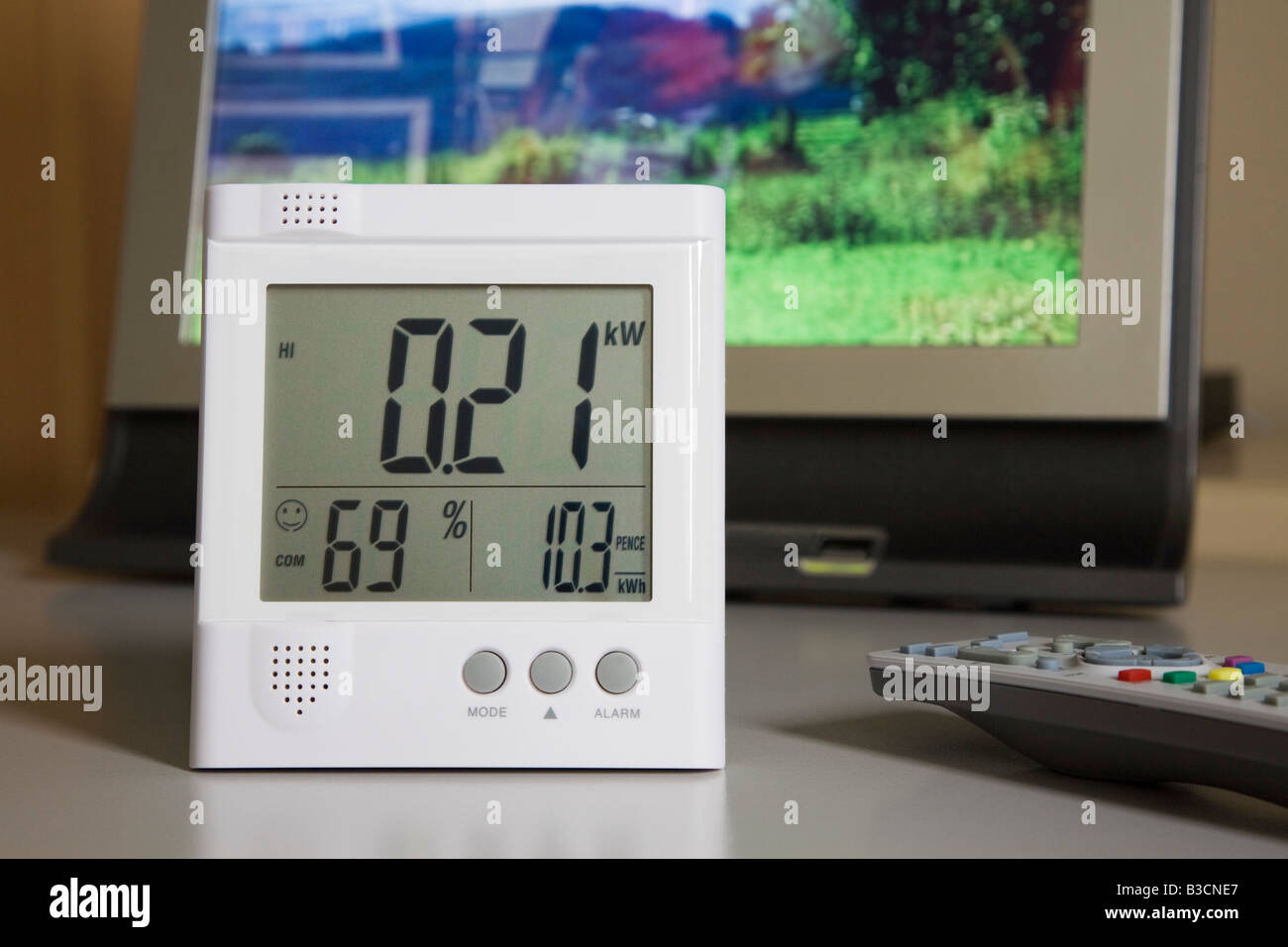Close up of wireless Owl energy monitor with LED display showing kilowatts of electricity being used by a flatscreen - Stock Image