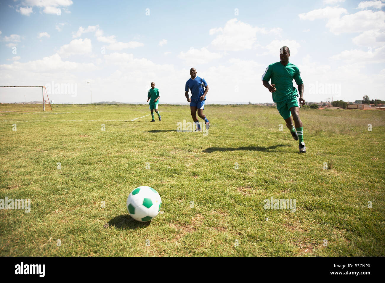 13MA-005 © Monkeyapple  aFRIKA Collection  Great Stock ! Team playing soccer on green field - Stock Image