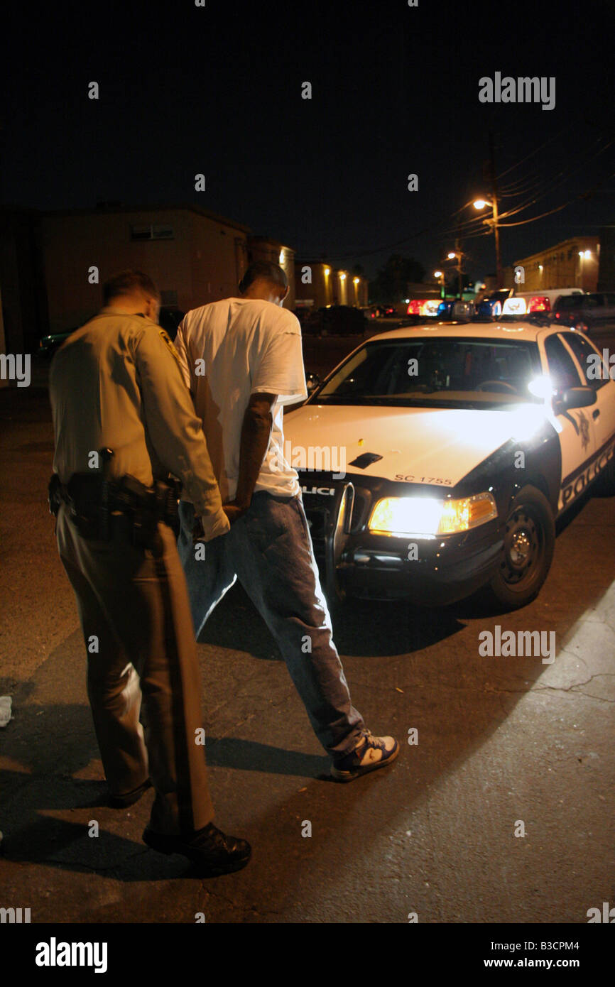 Las Vegas police officer searches a suspect at night - Stock Image
