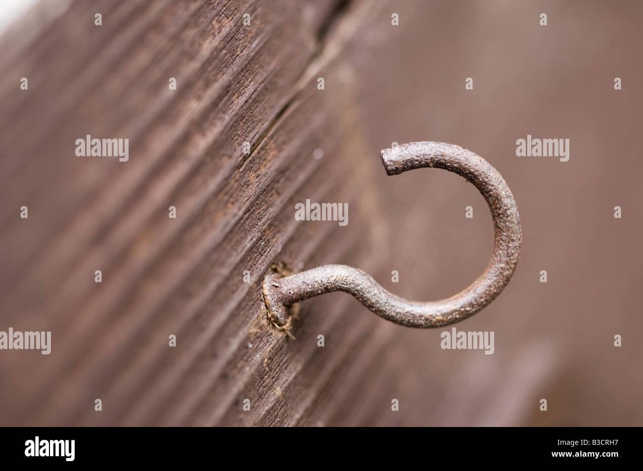 Rusty hook screwed into wood - Stock Image