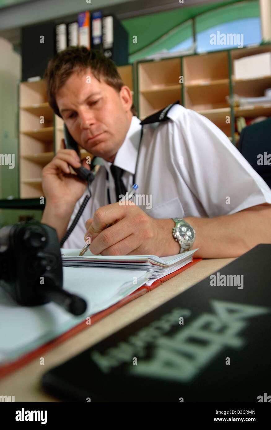 A SECURITY GUARD ANSWERS A PHONECALL AND MAKES AN ENTRY IN A LOG BOOK UK Stock Photo